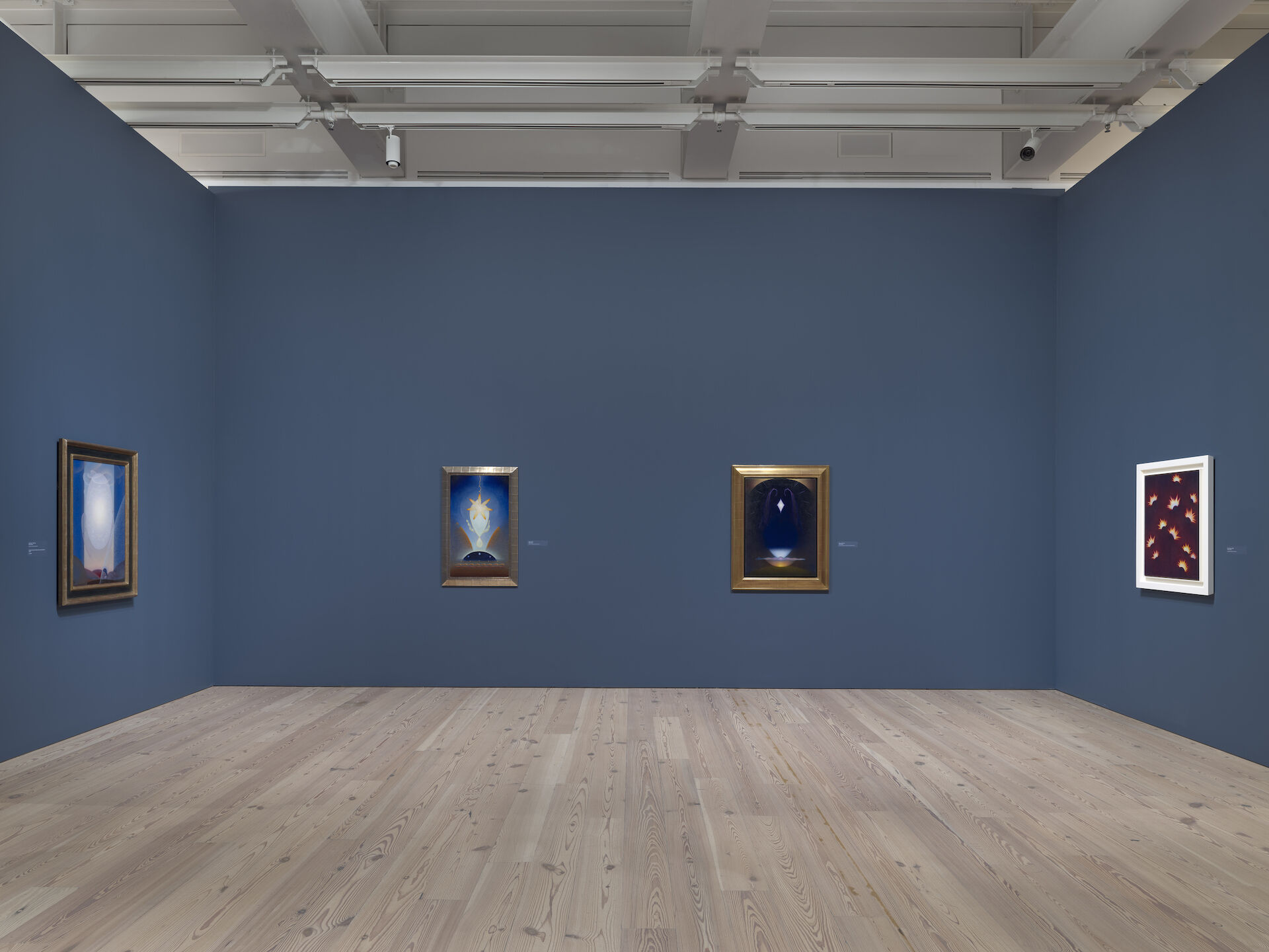 Looking into a blue room in the Whitney containing paintings by Agnes Pelton. From left to right: Light Center, 1947-48; Birthday, 1943; Alchemy, 1937-39; Fires in Space, 1938.