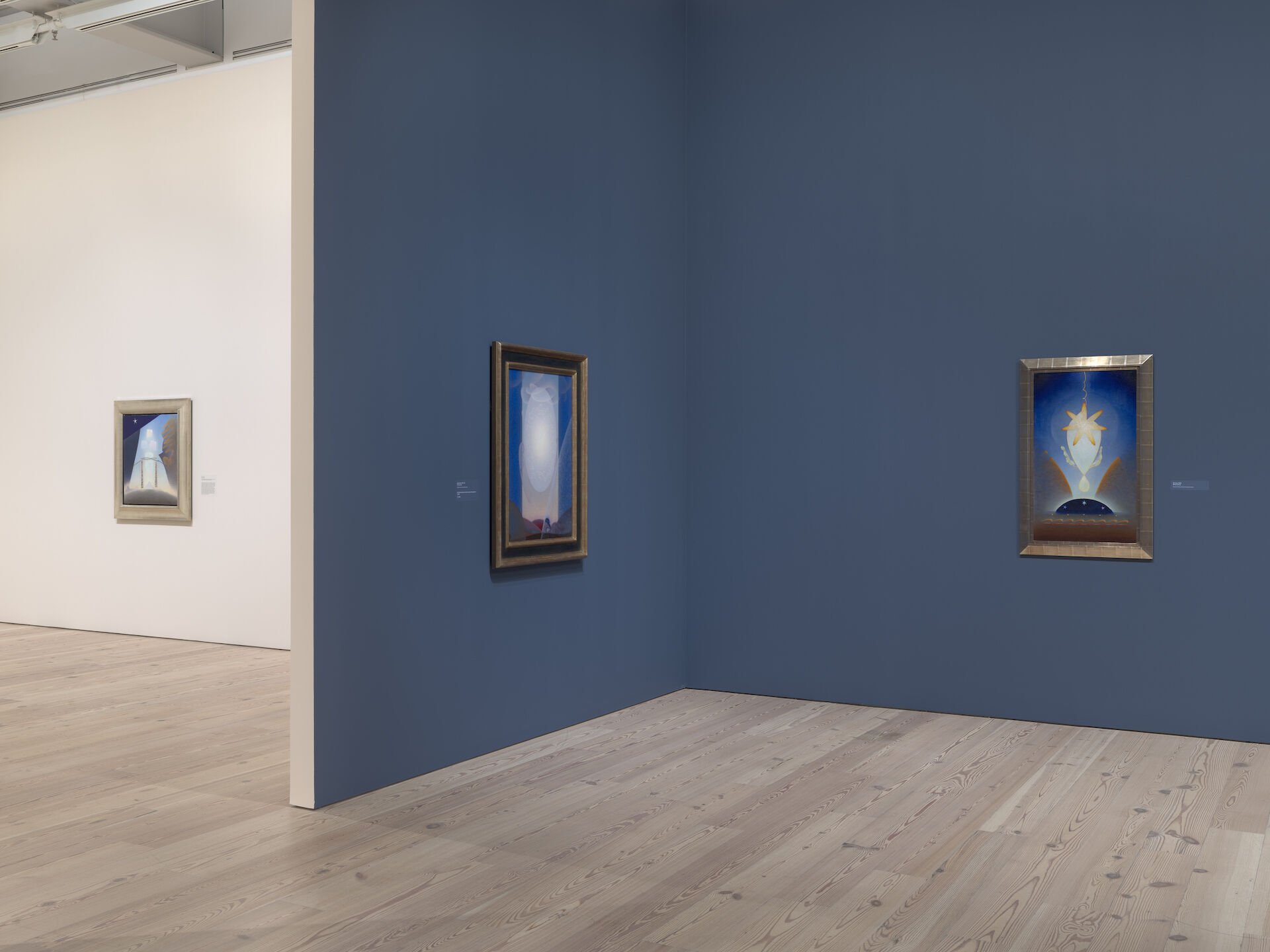 Looking from a blue room toward a white room to the left in the exhibition, Agnes Pelton: Desert Transcendentalist at the Whitney Museum of American Art. The work from left to right is Future, 1941; Light Center, 1947-48; and Birthday, 1943.