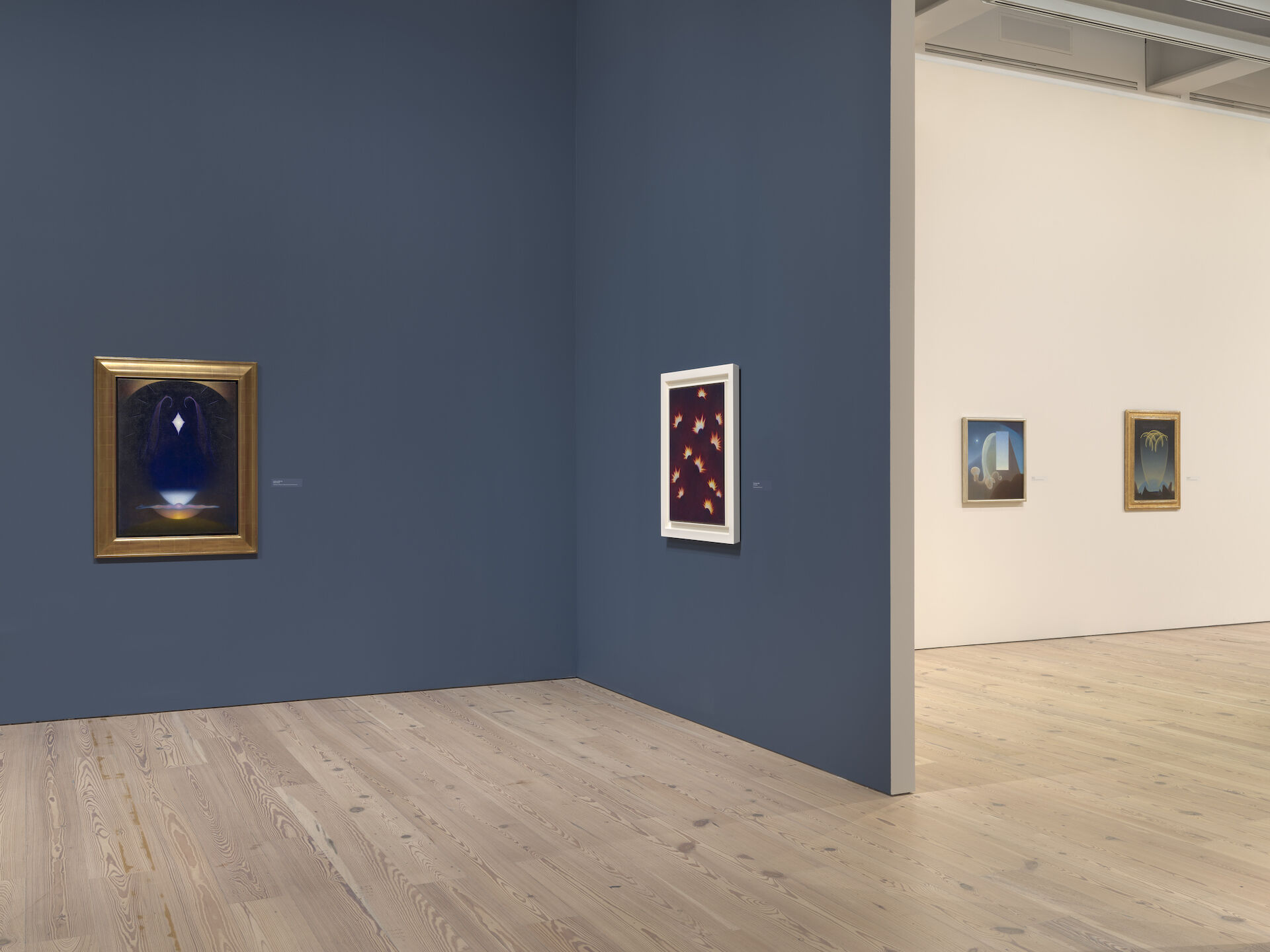 In a blue room at the Whitney, two paintings appear on walls to the right of a white room containing two other paintings. The work is by Agnes Pelton, from left to right: Alchemy, 1937-39; Fires in Space, 1938; Day, 1935; Messengers, 1932.