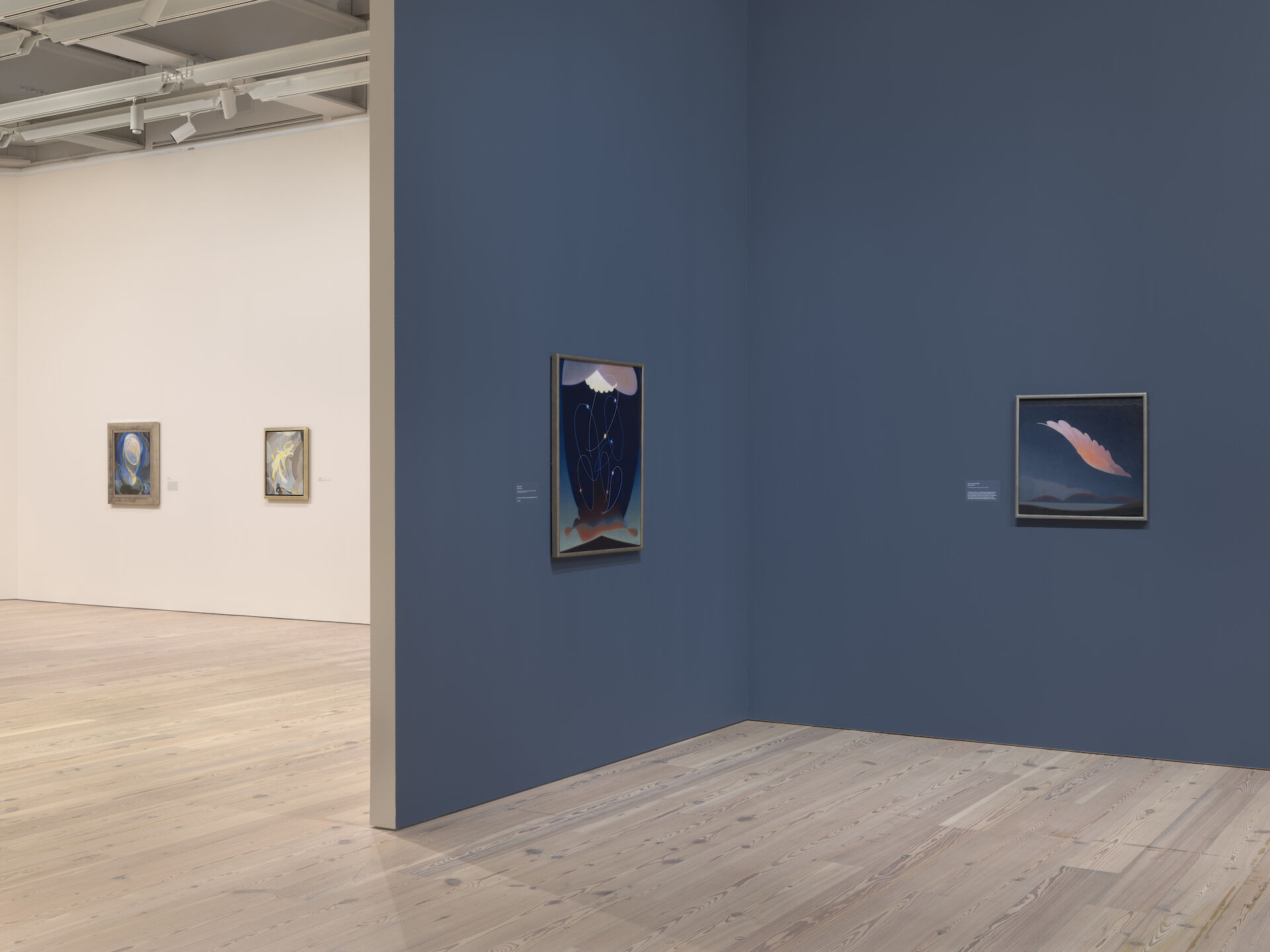 A white room appears further back to the left of a blue room. Two paintings are visible in each room in the exhibition, Agnes Pelton: Desert Transcendentalist. The work from left to right is: Being, 1926; Ecstasy, 1928; Orbits, 1934; and The Primal Wing, 1933.