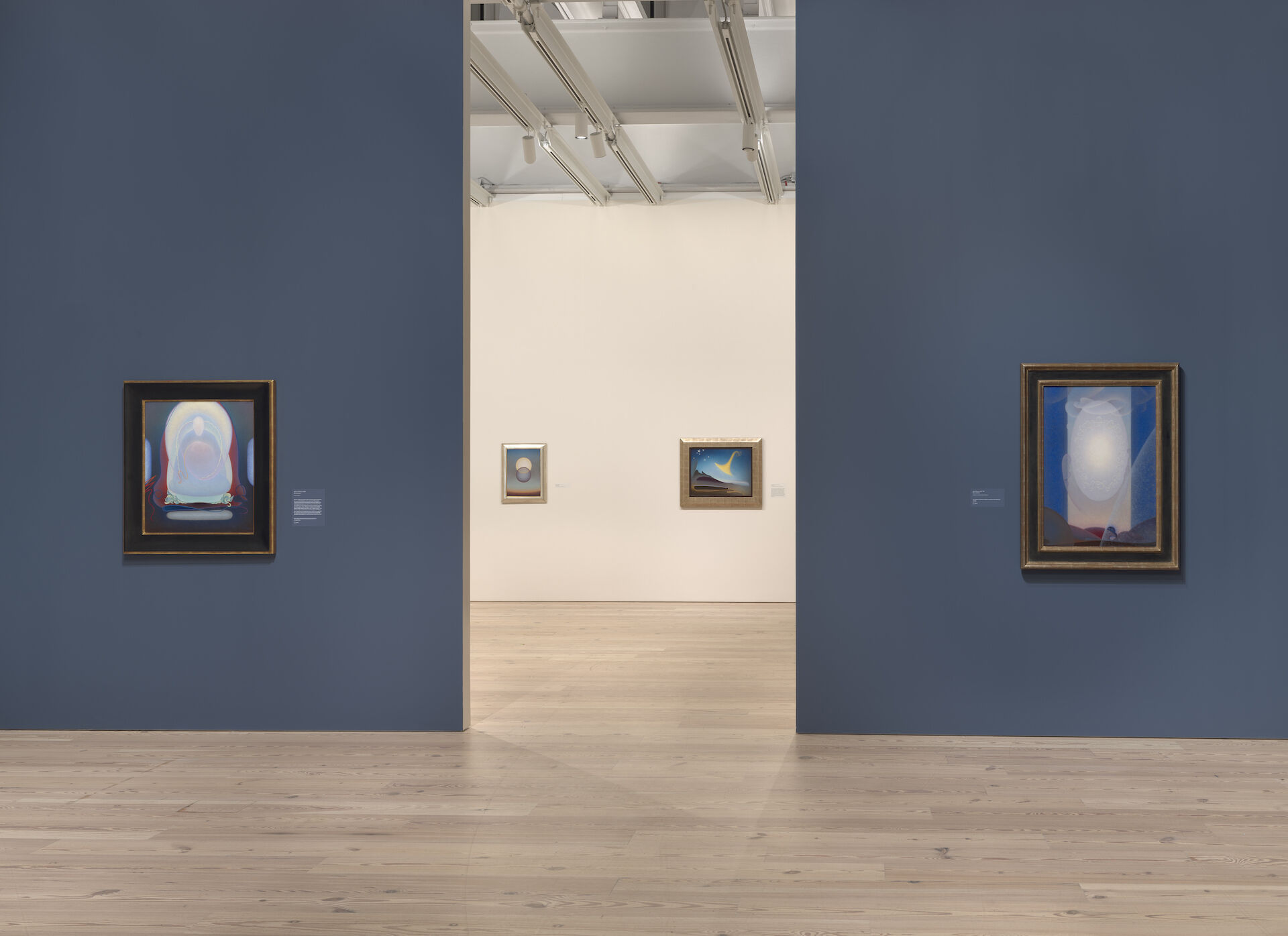 There is an entryway between two blue walls with a painting on each side. Past the entryway is a white room with paintings against the back wall. Each painting is by Agnes Pelton at the Whitney. From left to right: Mother of Silence, 1933; Departure, 1952; Awakening (Memory of Father), 1943; Light Center, 1947-48.