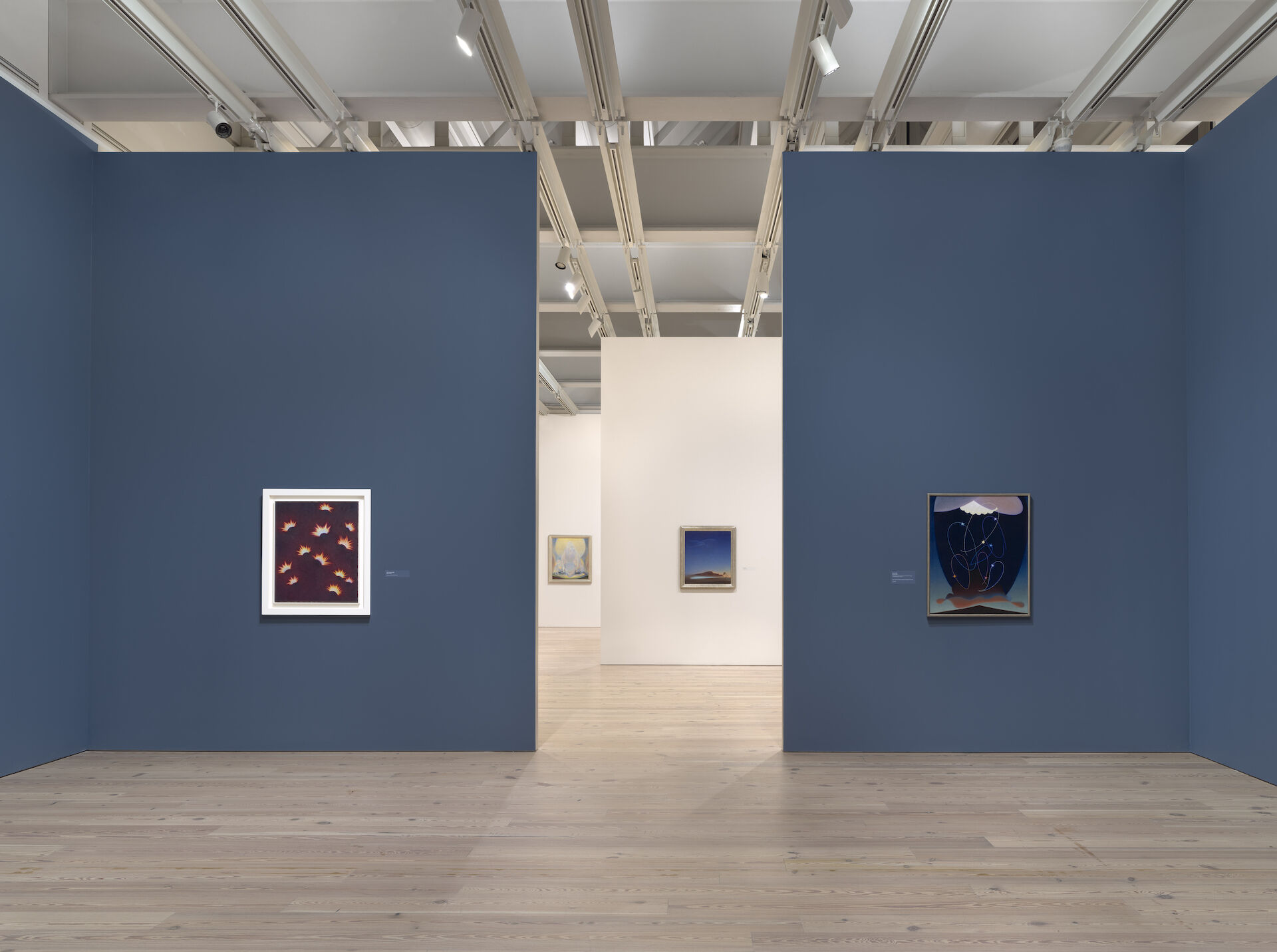 There is an entryway between two blue walls with a painting on each side. Past the entryway is a white room with paintings against the back wall. Each painting is by Agnes Pelton at the Whitney. From left to right: Fires in Space, 1938; The Fountains, 1926; Return, 1940; Orbits, 1934.