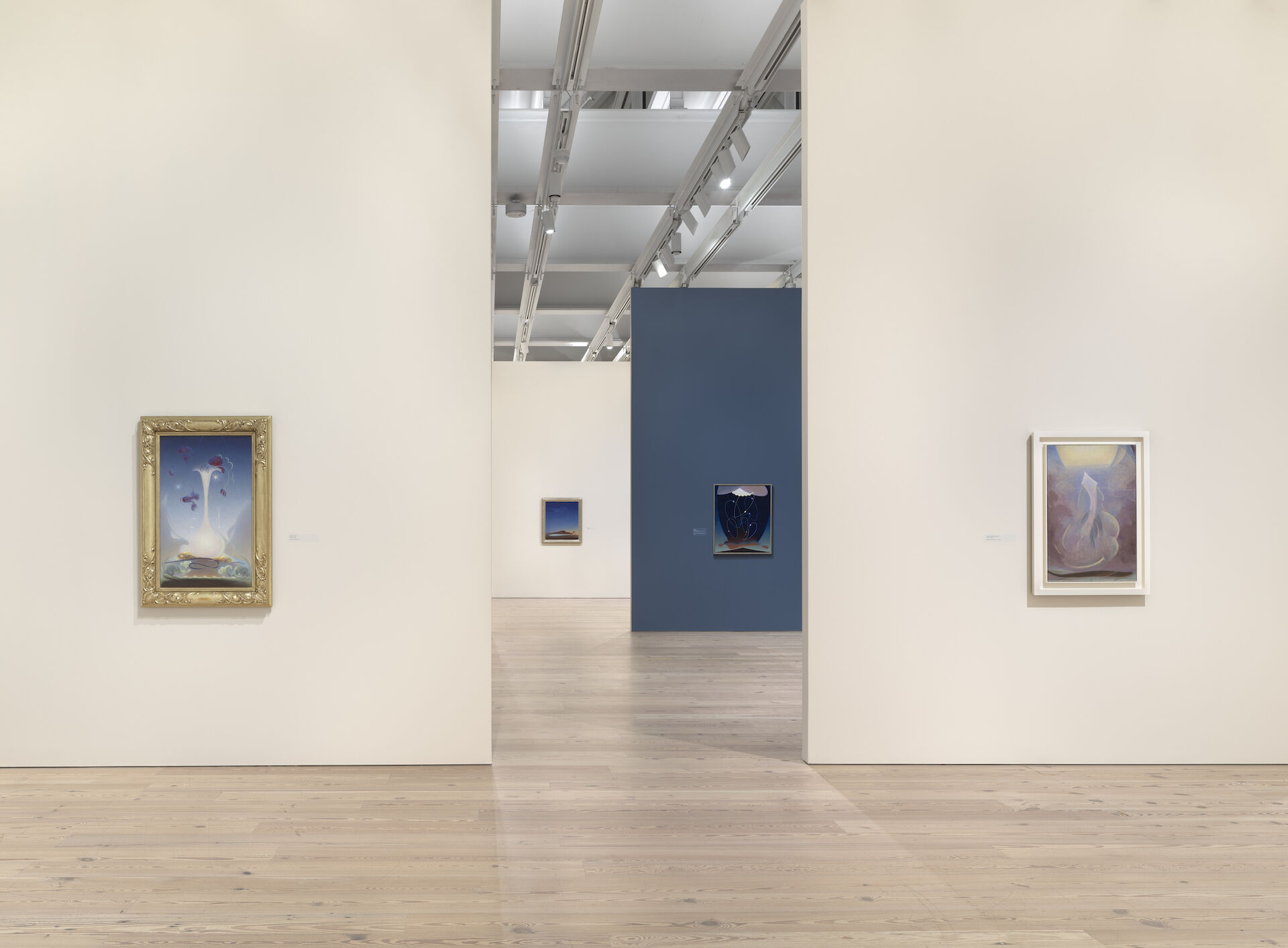 Two white walls appear at the forefront of the gallery, framed by two Agnes Pelton paintings, Memory, 1937 to the left and Ascent (Liberation), 1946 to the right.