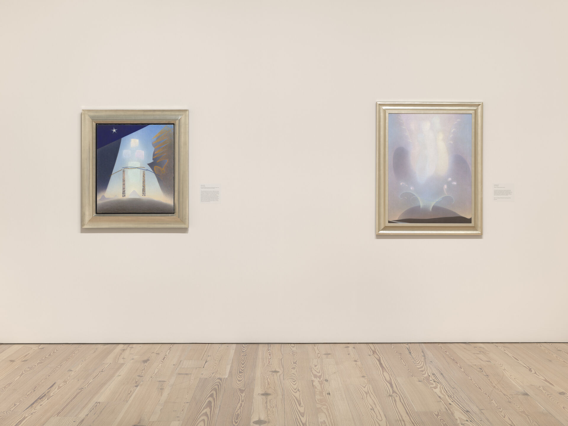 Two paintings by Agnes Pelton appear directly ahead on a white wall of the Whitney. From left to right: Future, 1941; The Blest, 1941.