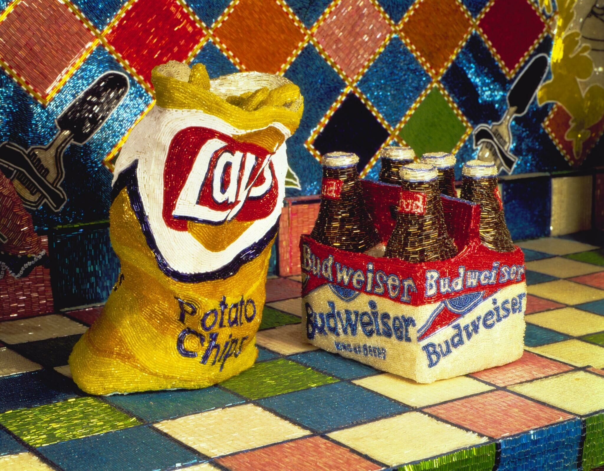 A beaded bag of chips and pack of beer on top of a beaded countertop.