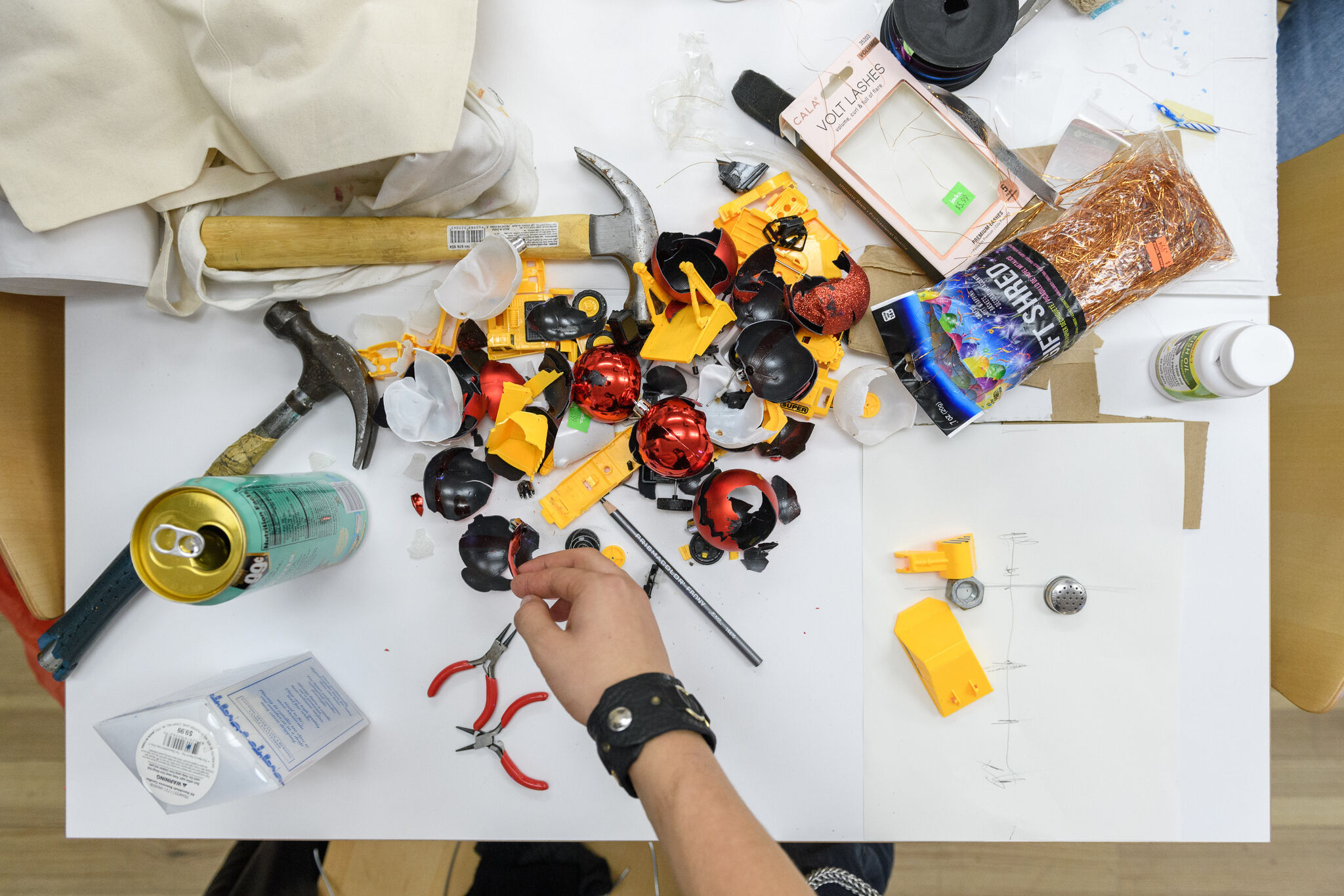 Broken pieces of what appears to be plastic and metal and ornaments rest on a white table next to hammers, glue, and pliers. A hand with a black bracelet is reaching toward some of these materials.