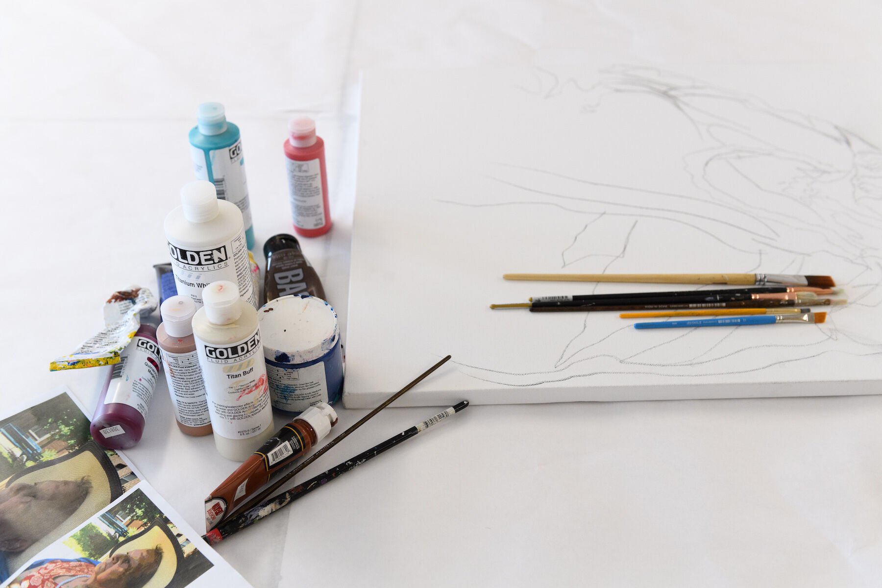 Art materials rest on a white table