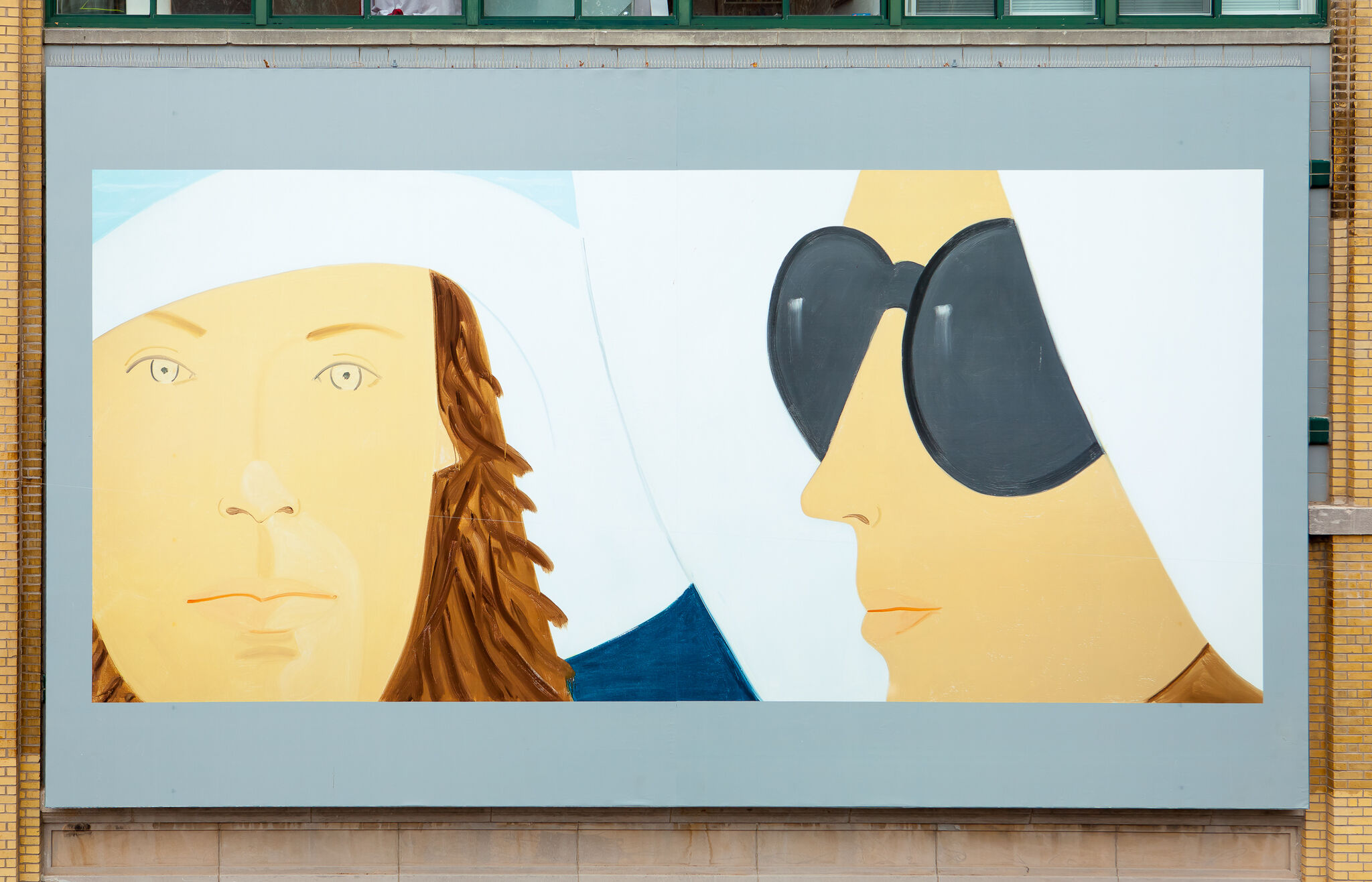 A billboard showing a close-up view of two people's faces.