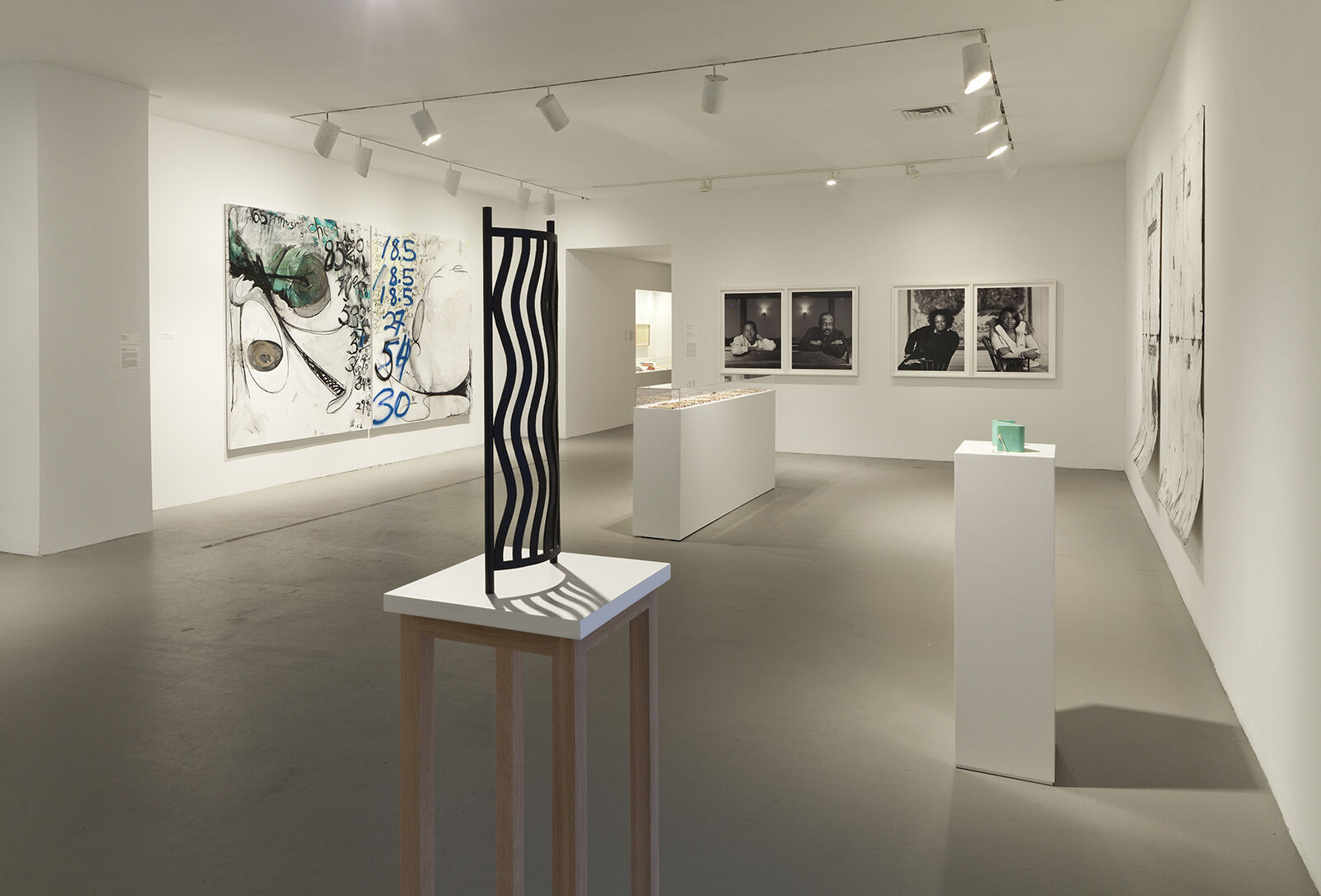An exhibition gallery with a sculpture on display and works of art on the walls.