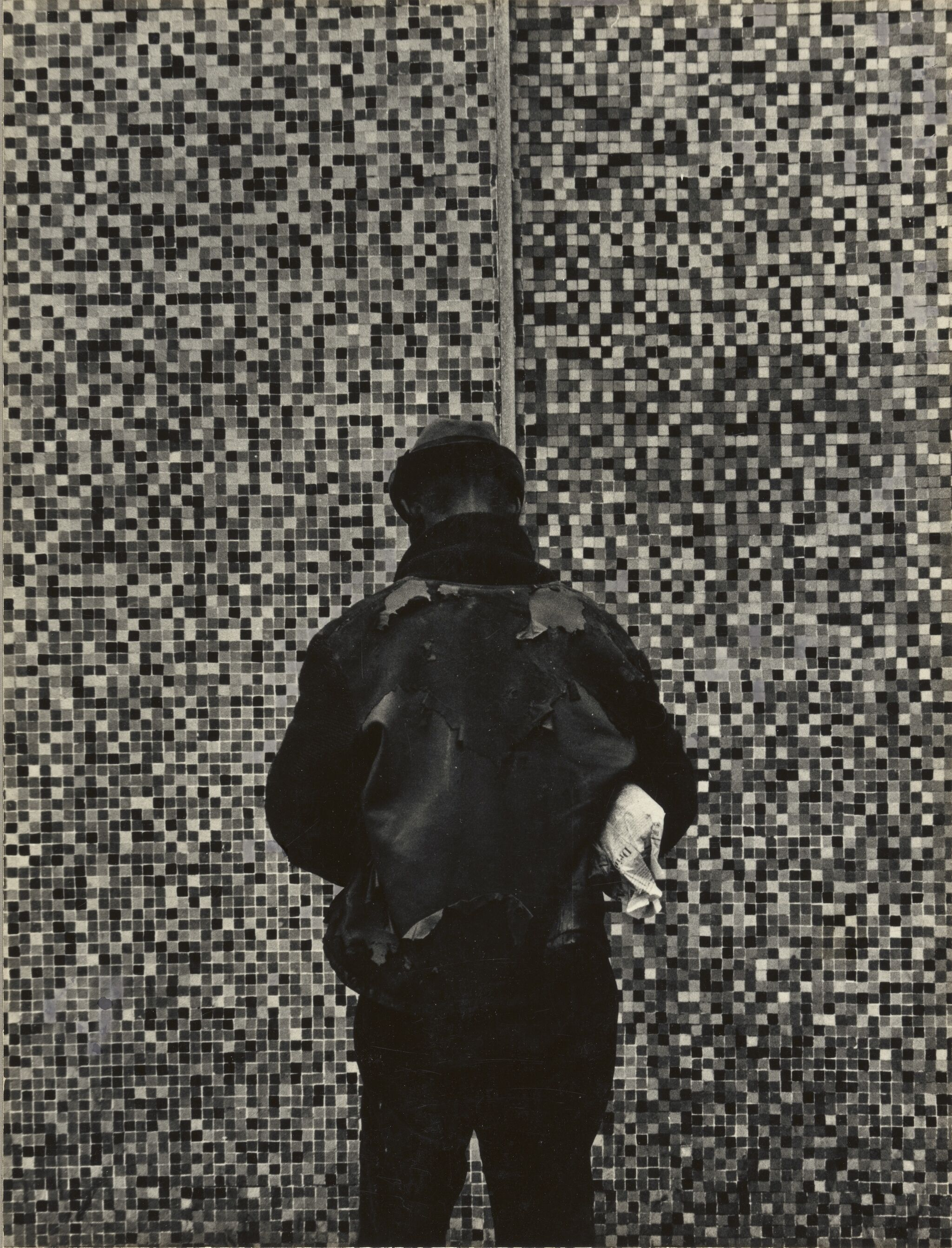 A person wearing a fedora and backpack is turned away, facing a tiled wall.