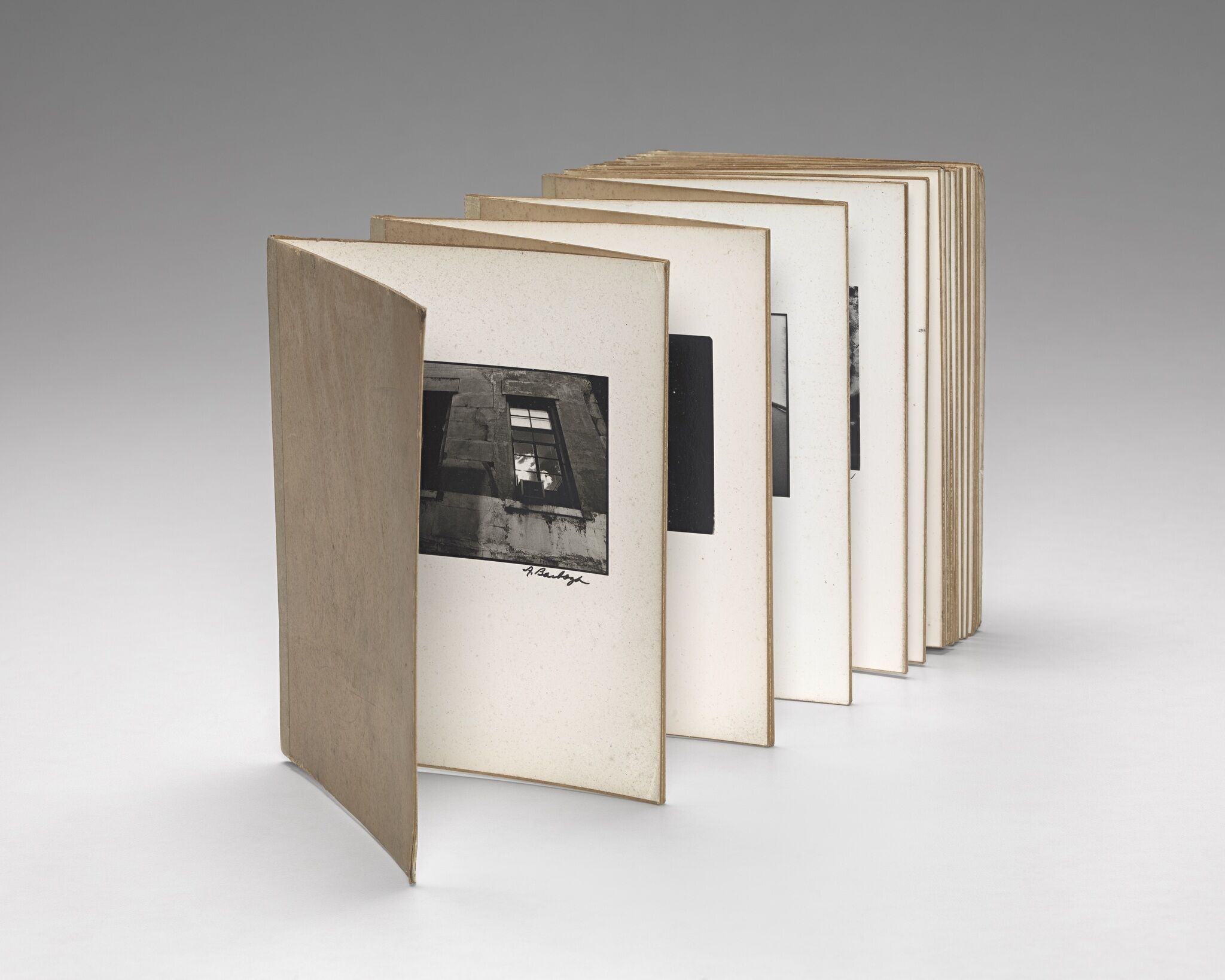 An accordion book of black and white photographs.