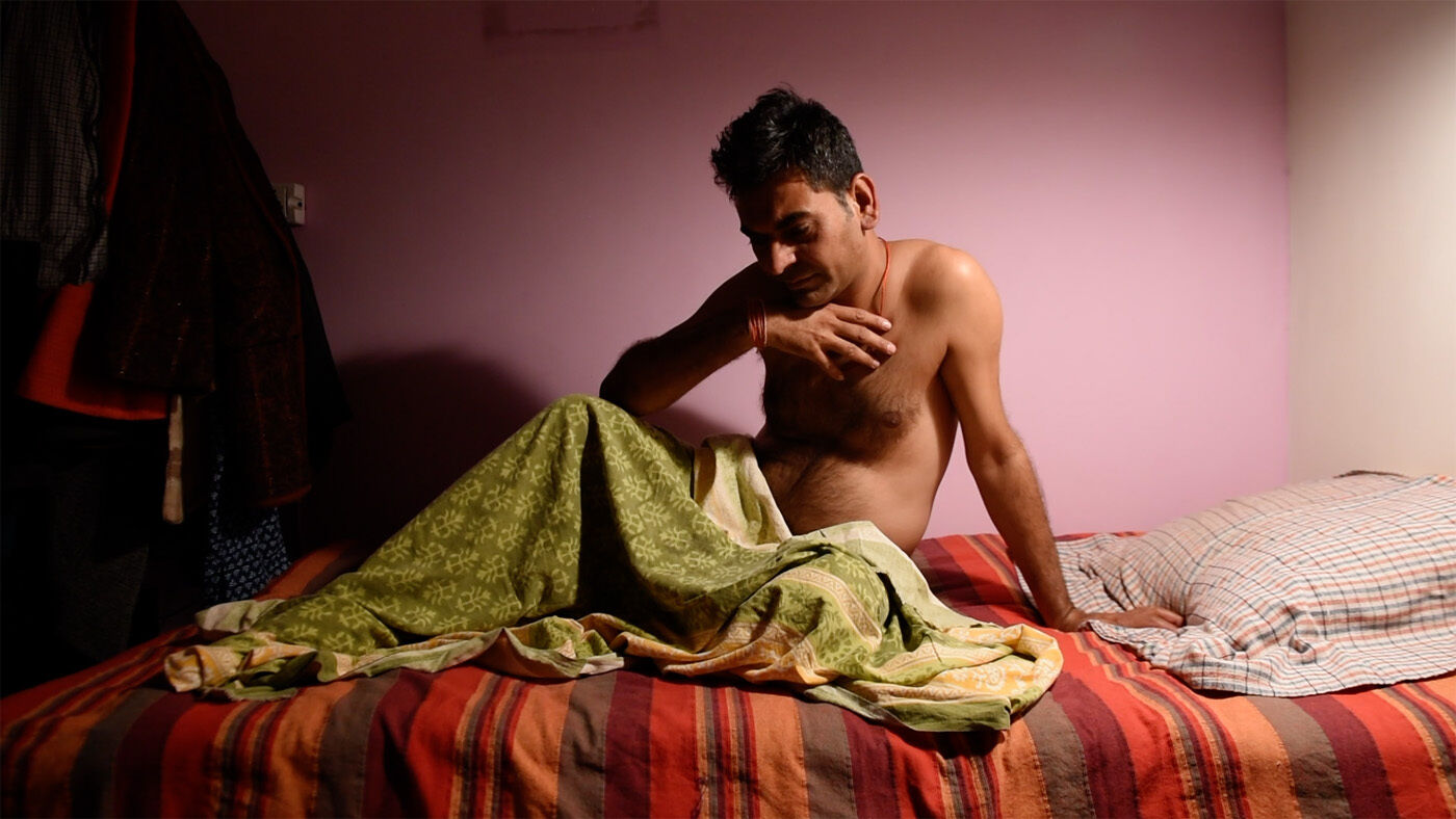 An Indian person with short hair sits in bed, shirtless with a green blanket over their lap and one hand to their chest.