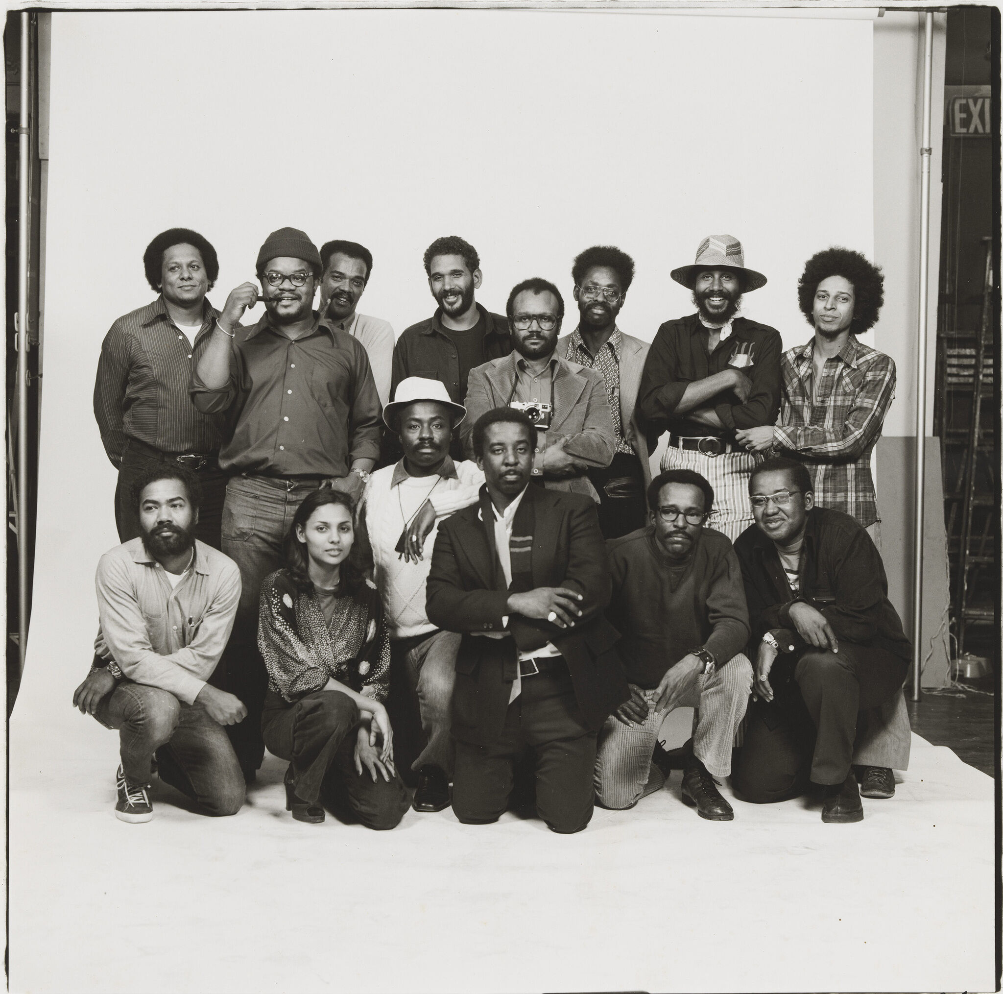 Fourteen members of the Kamoinge Workshop—all Black photographers—pose in two rows for a group portrait