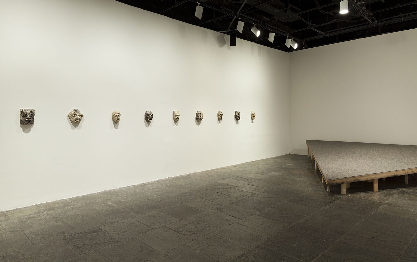 A gallery with masks displayed in a line across a wall.