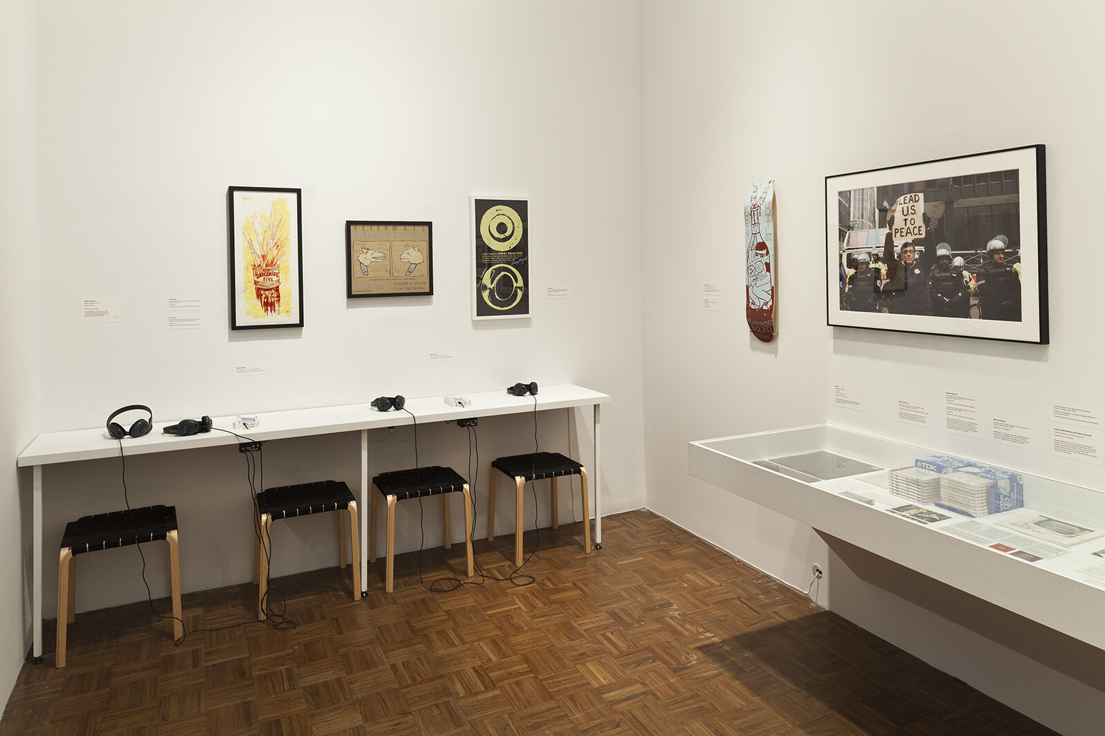 A gallery filled with works of art and a table with several pairs of headphones.