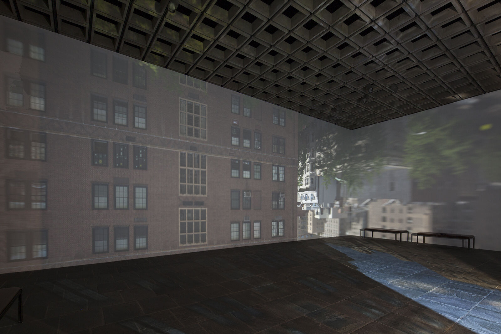A gallery with walls showing an upside down view of a street.