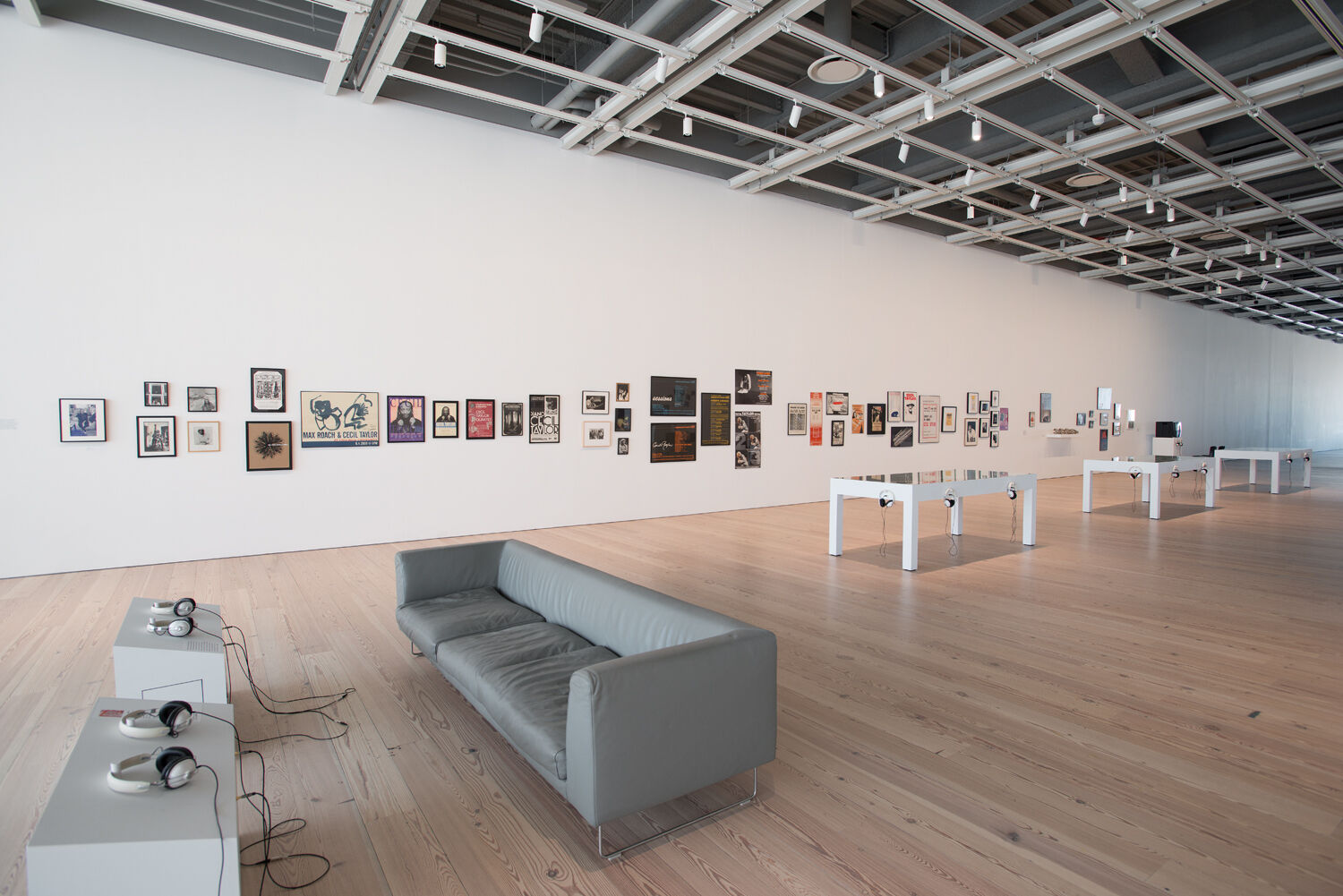 A gallery with a couch and art on the wall.