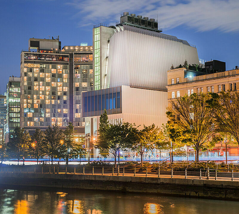 The Whitney Museum lit up in the early evening, viewed from the Hudson River.