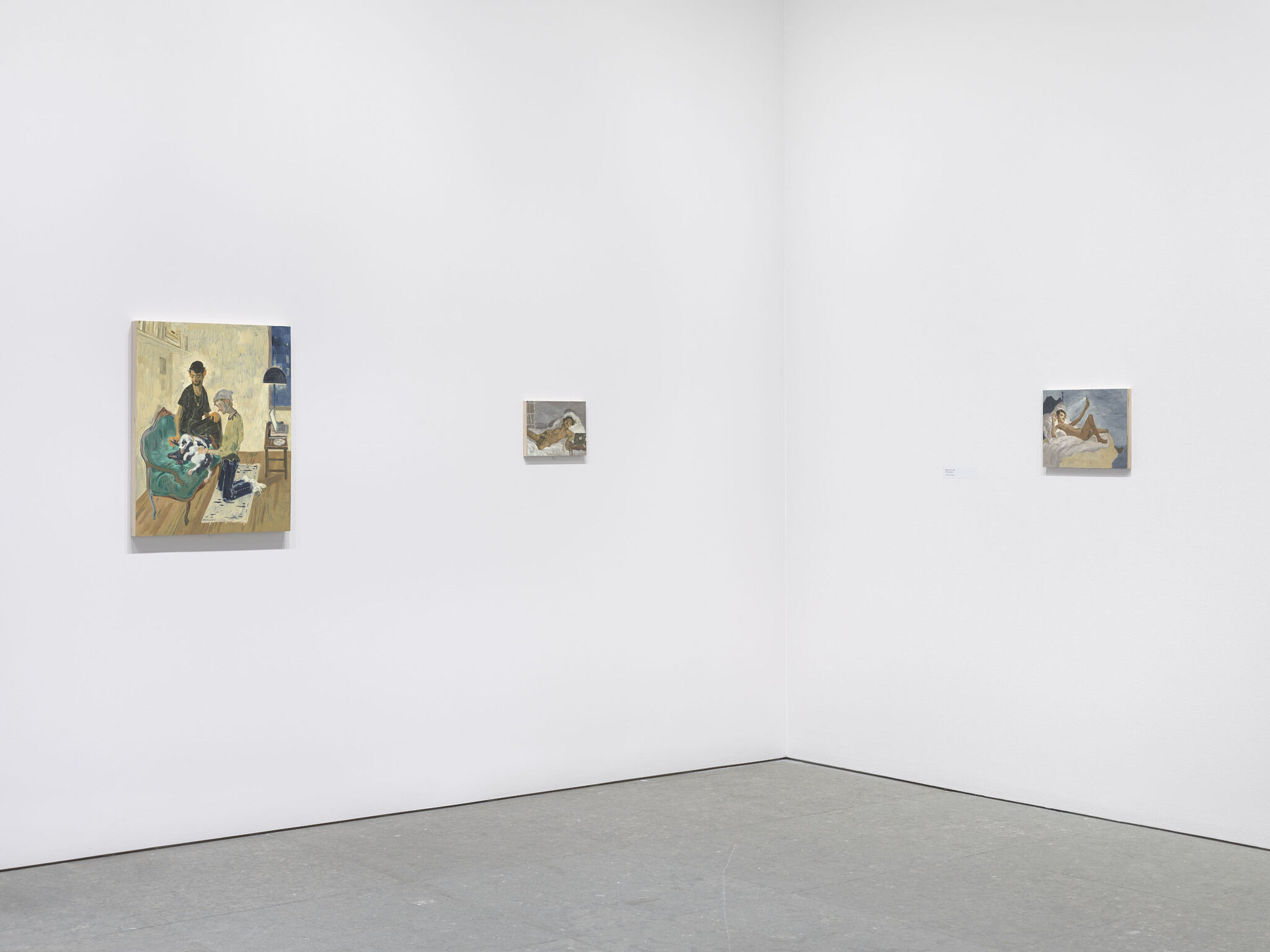 A corner of a gallery with art on the walls.
