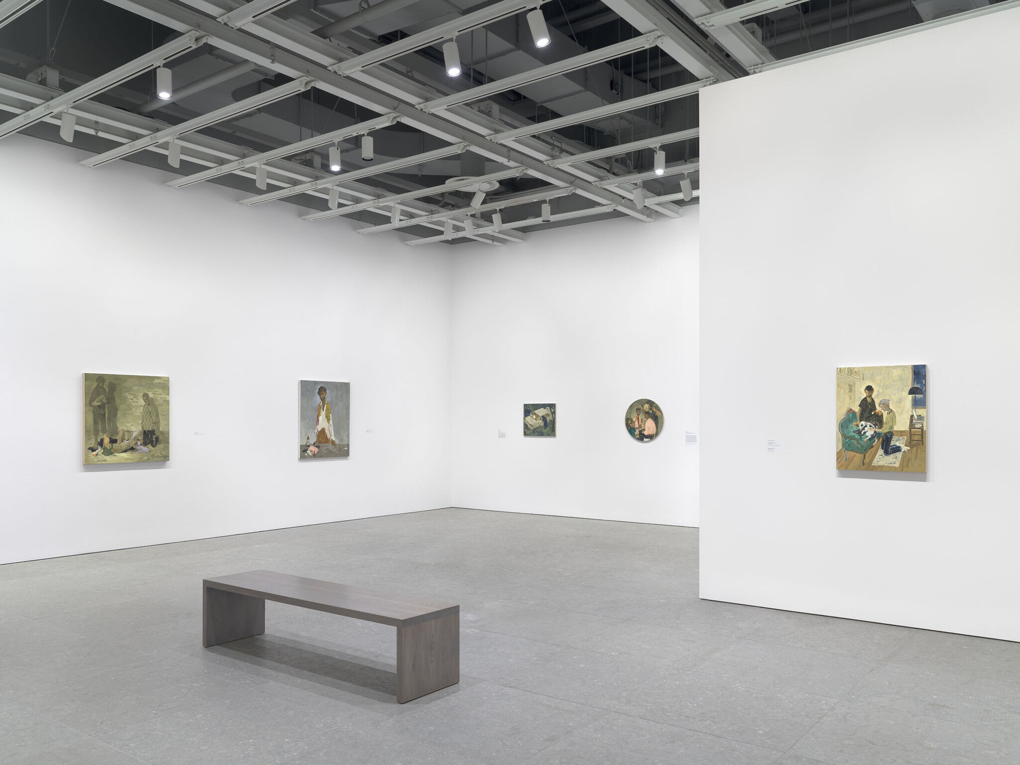 A gallery with a bench and art on the walls.