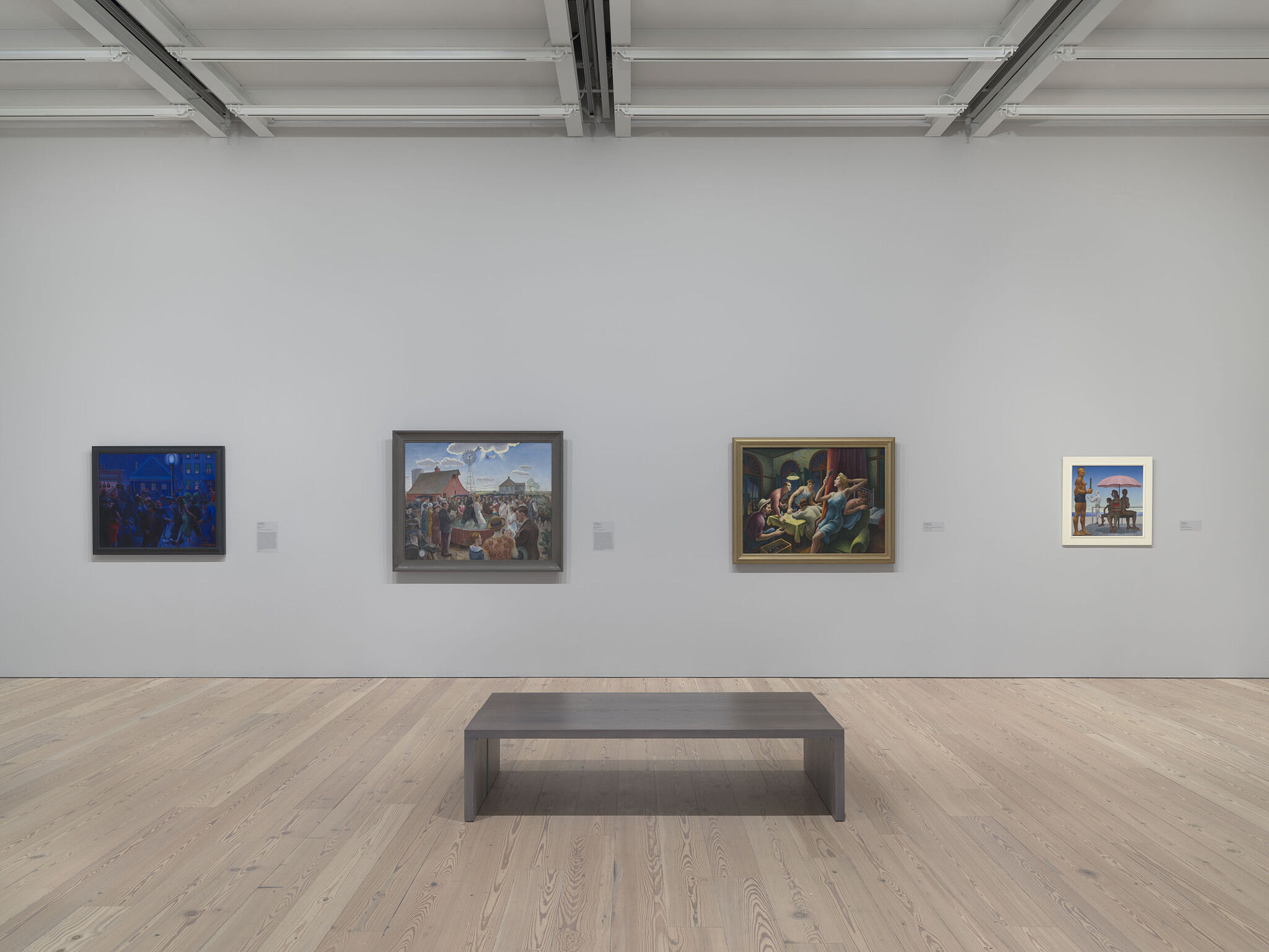 A gallery with a bench and art on the wall.