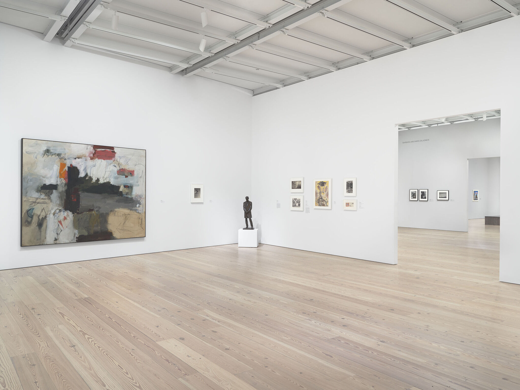 A gallery with a sculpture on display and works of art on the walls.