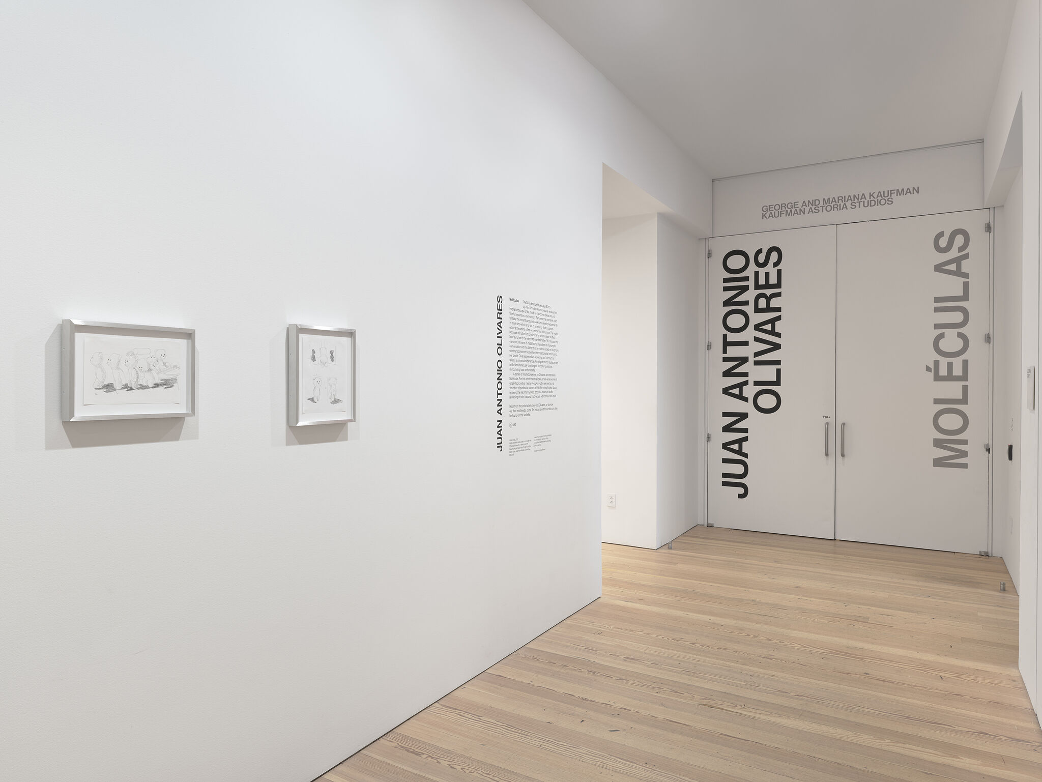 A gallery with works of art and wall text.