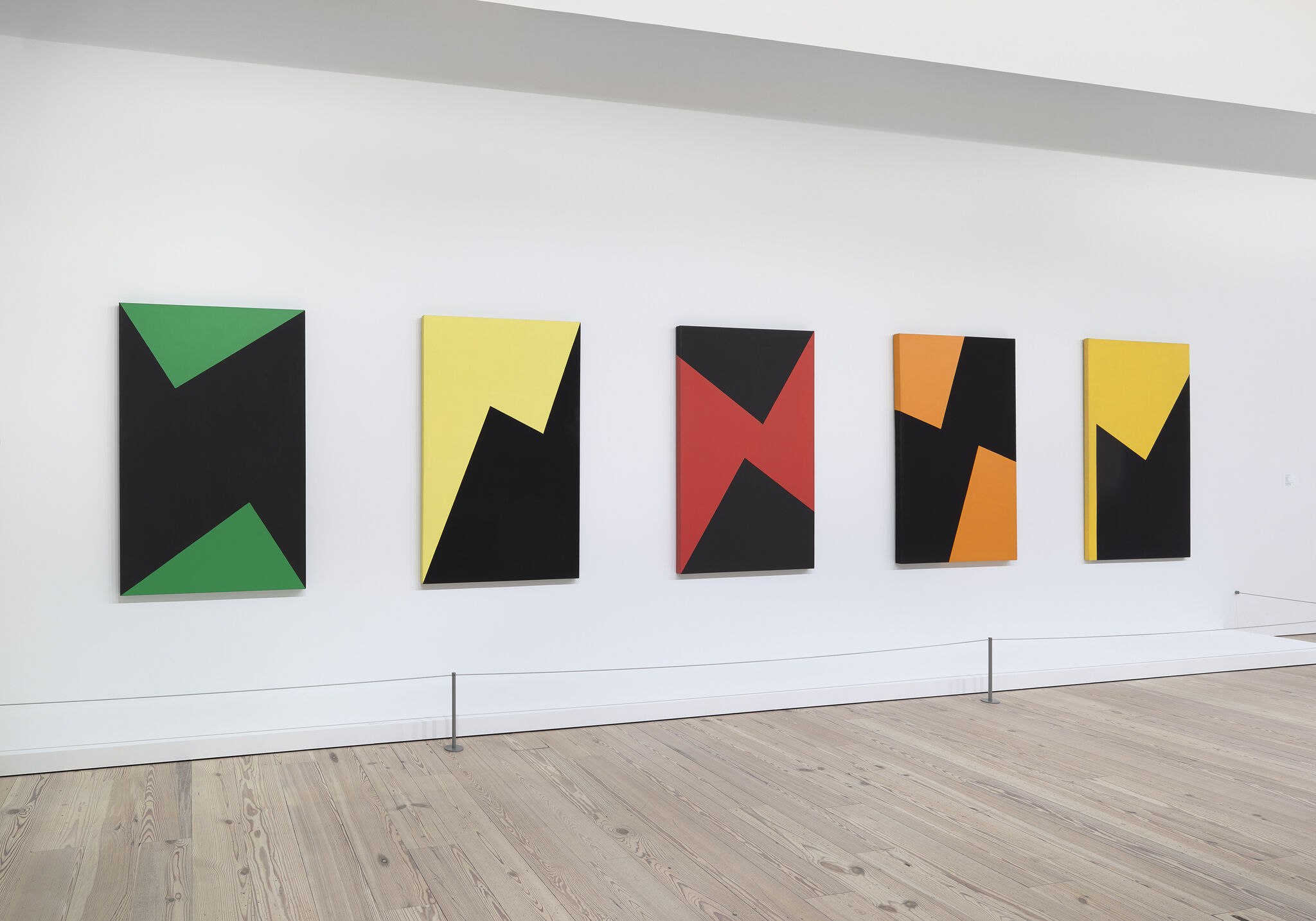 A gallery wall displaying five works of art in a row.