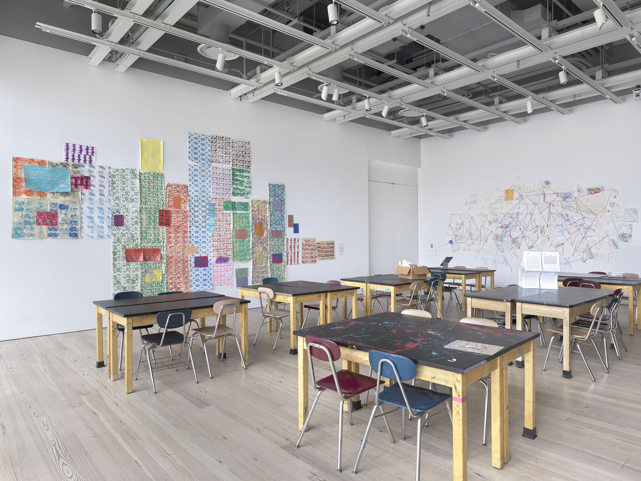 An installation view of a classroom with art.