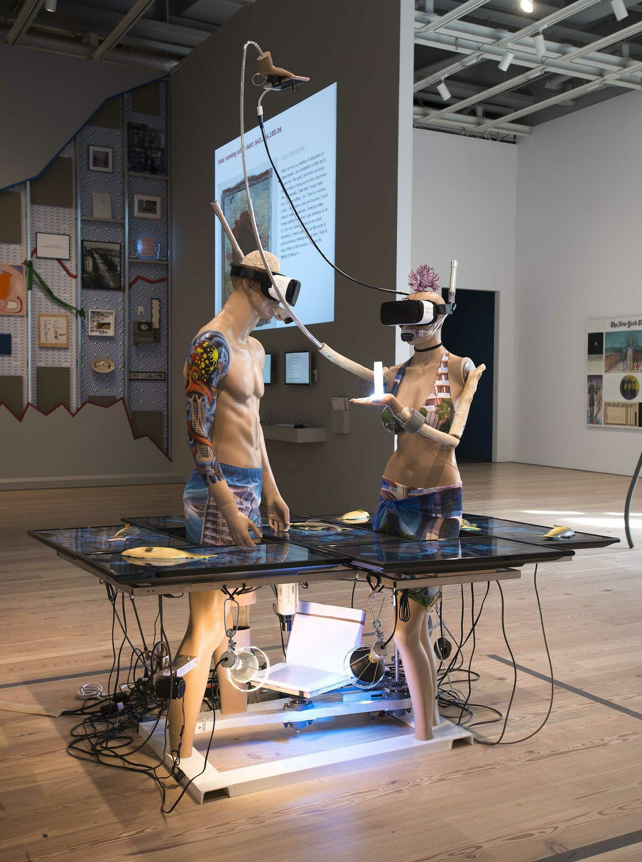 Two sculptures of figures wearing VR headsets displayed in a gallery.