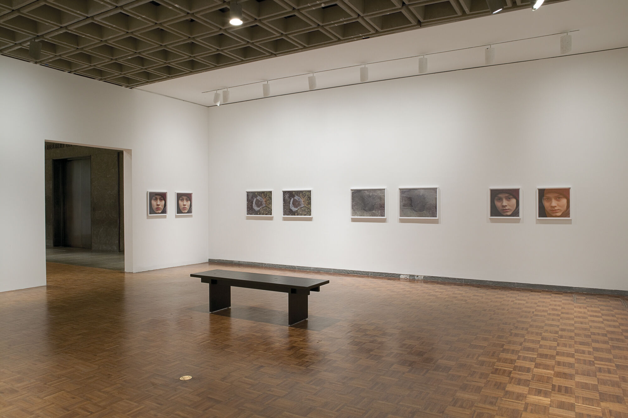 Works of art displayed in a gallery with a bench.