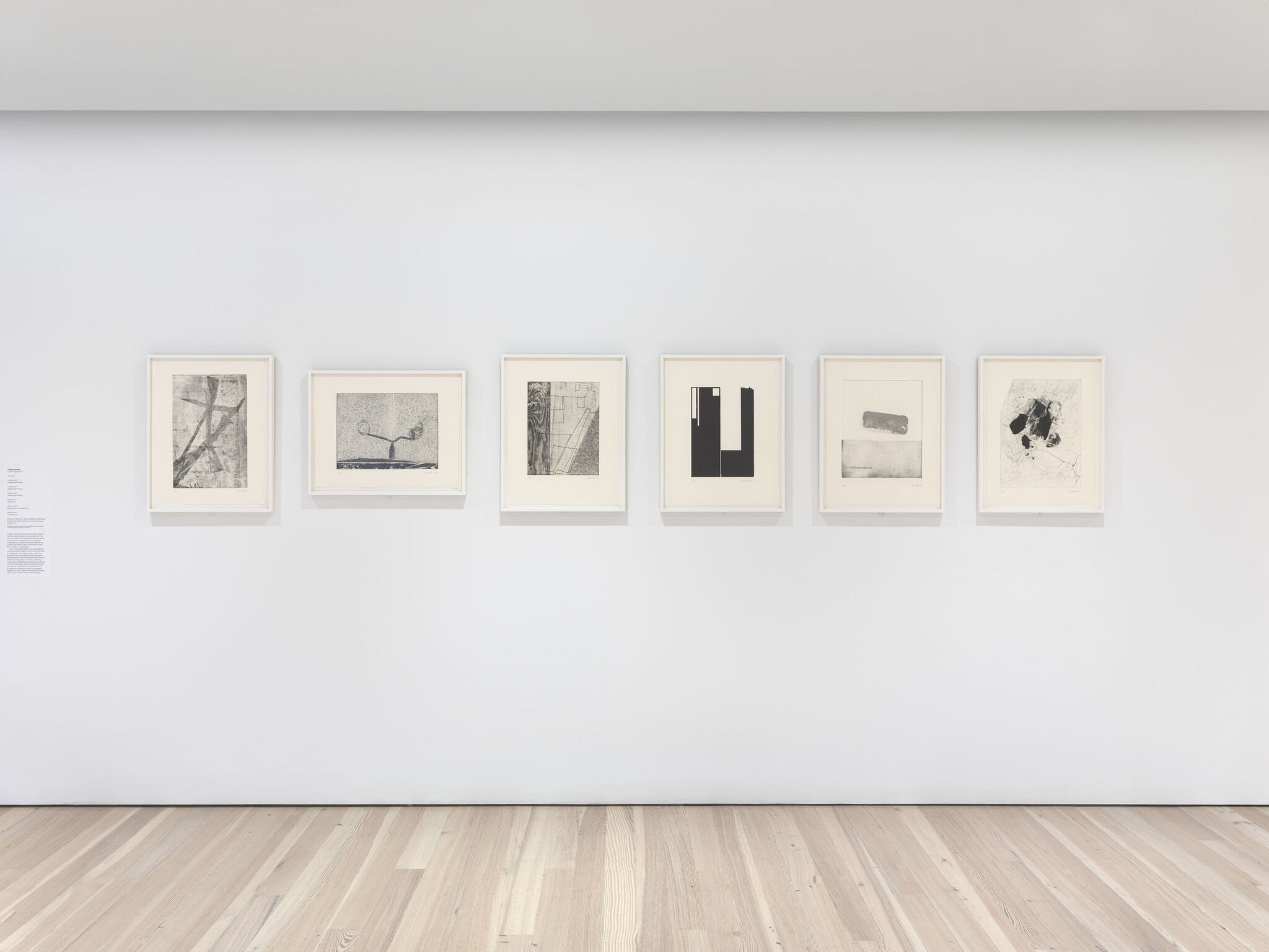 Six works of art displayed in a row on a white wall.