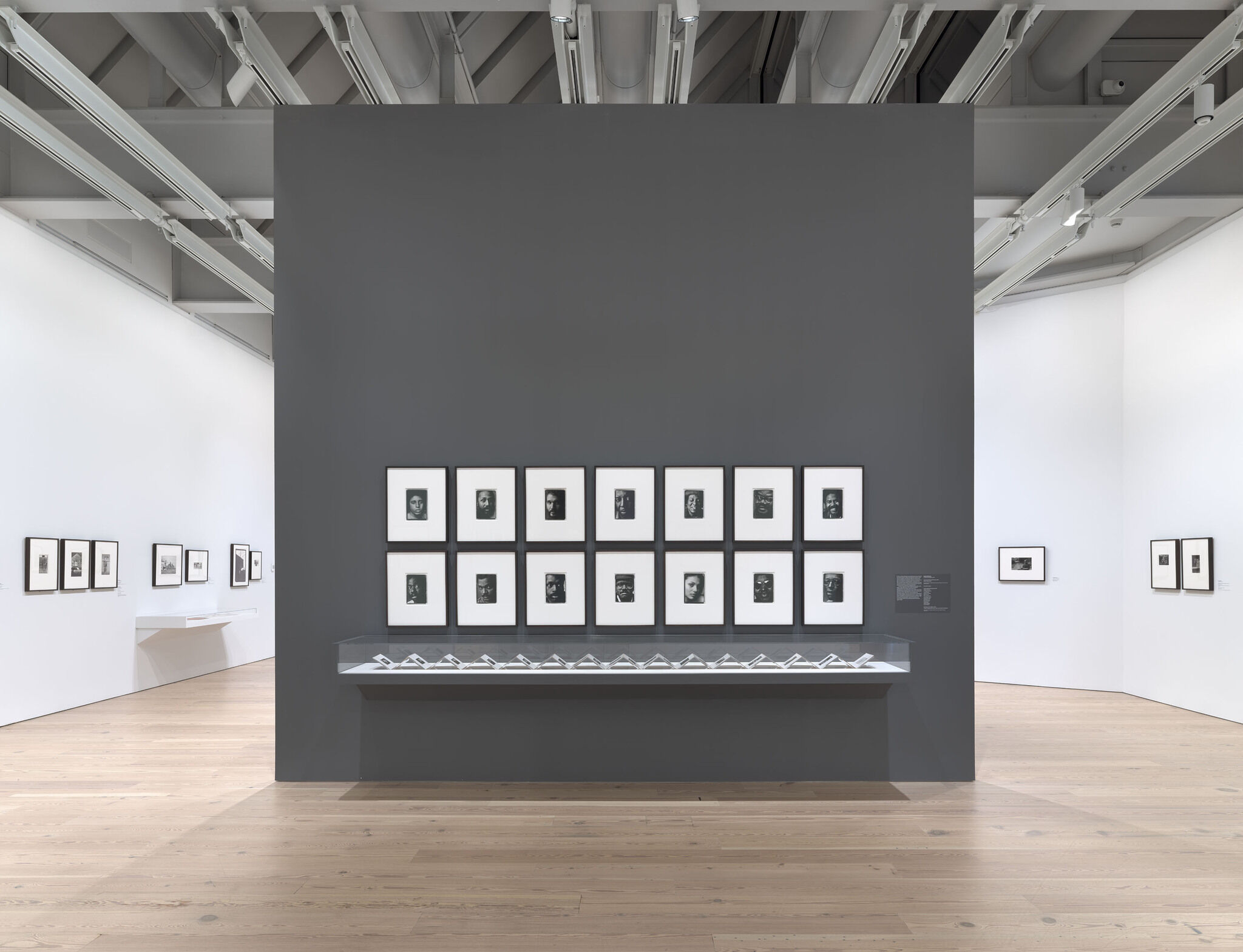 Black and white portraits displayed on a wall in a gallery.