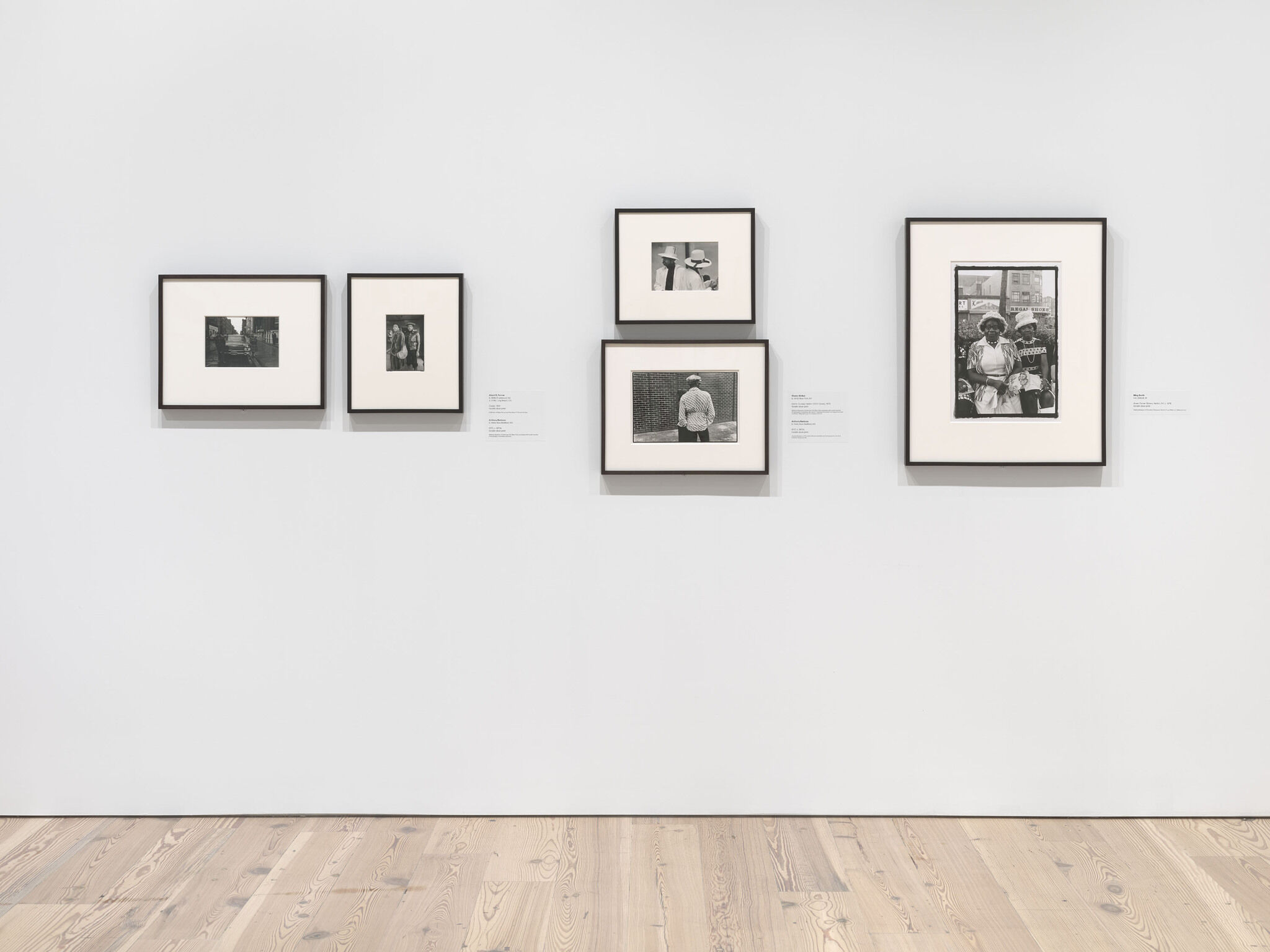 Black and white photos displayed in frames on a wall in a gallery.