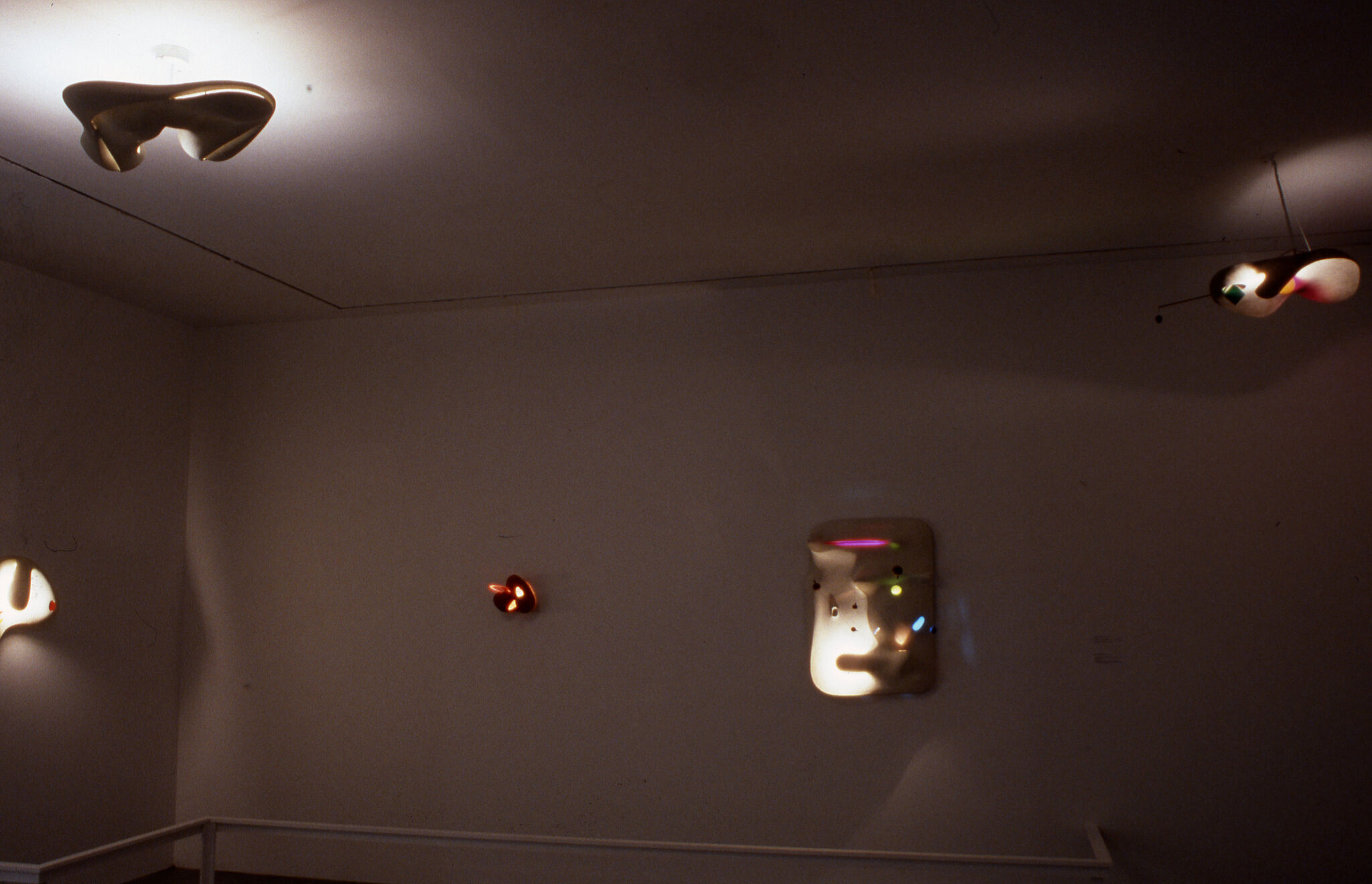 A dimly lit gallery with sculptures.