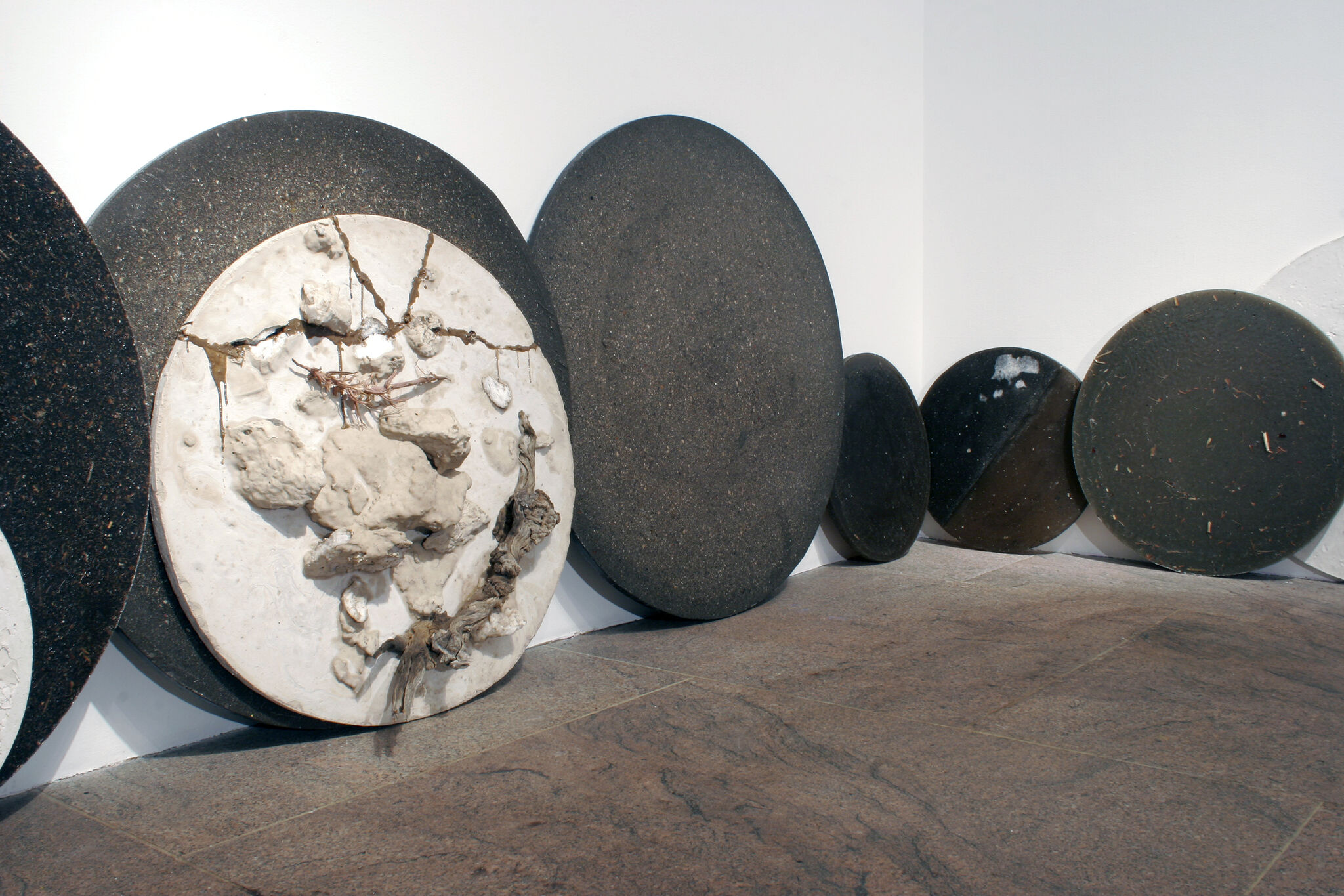 Circular stone sculptures leaned against a wall in a gallery.
