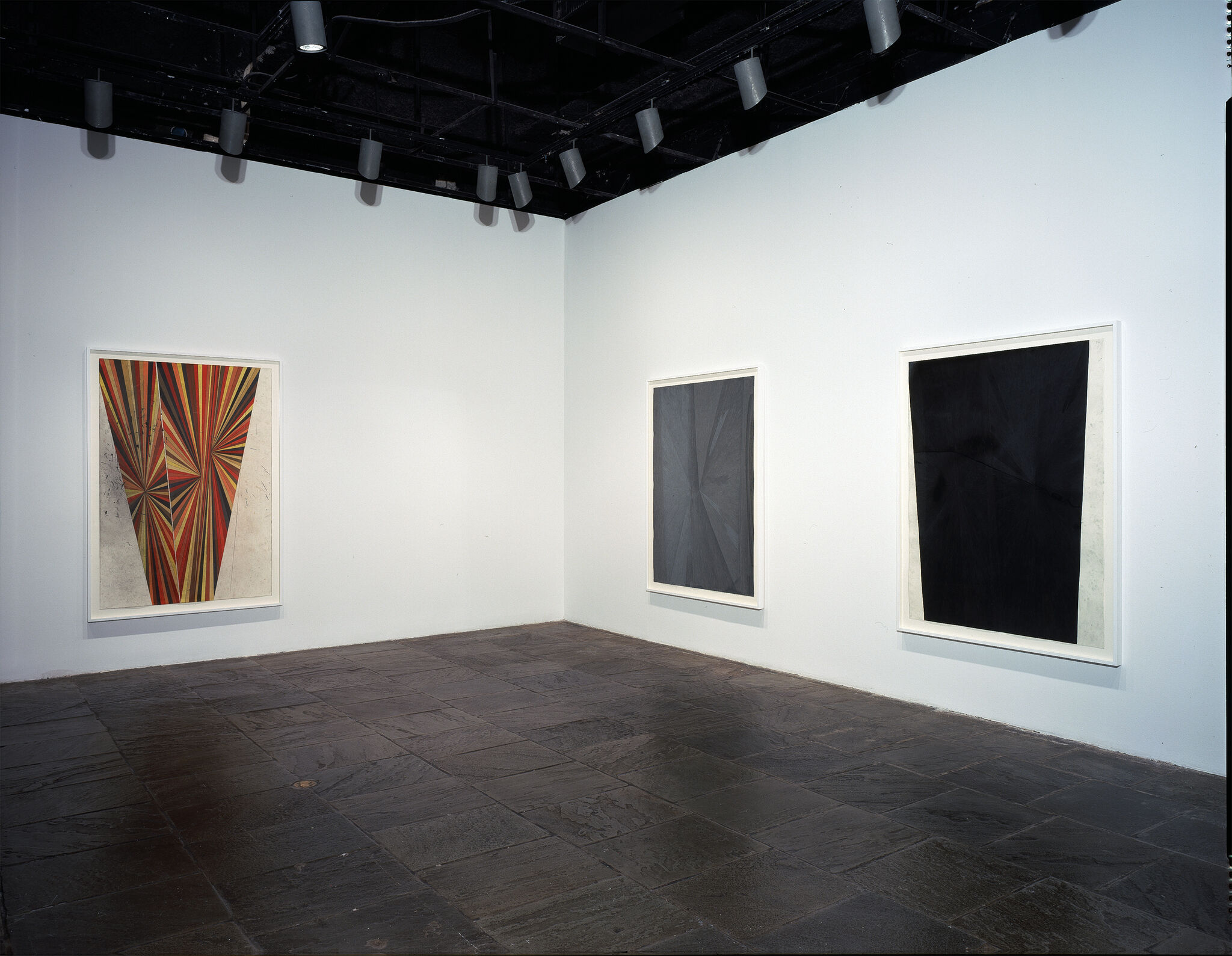 Three abstract paintings displayed in a gallery.