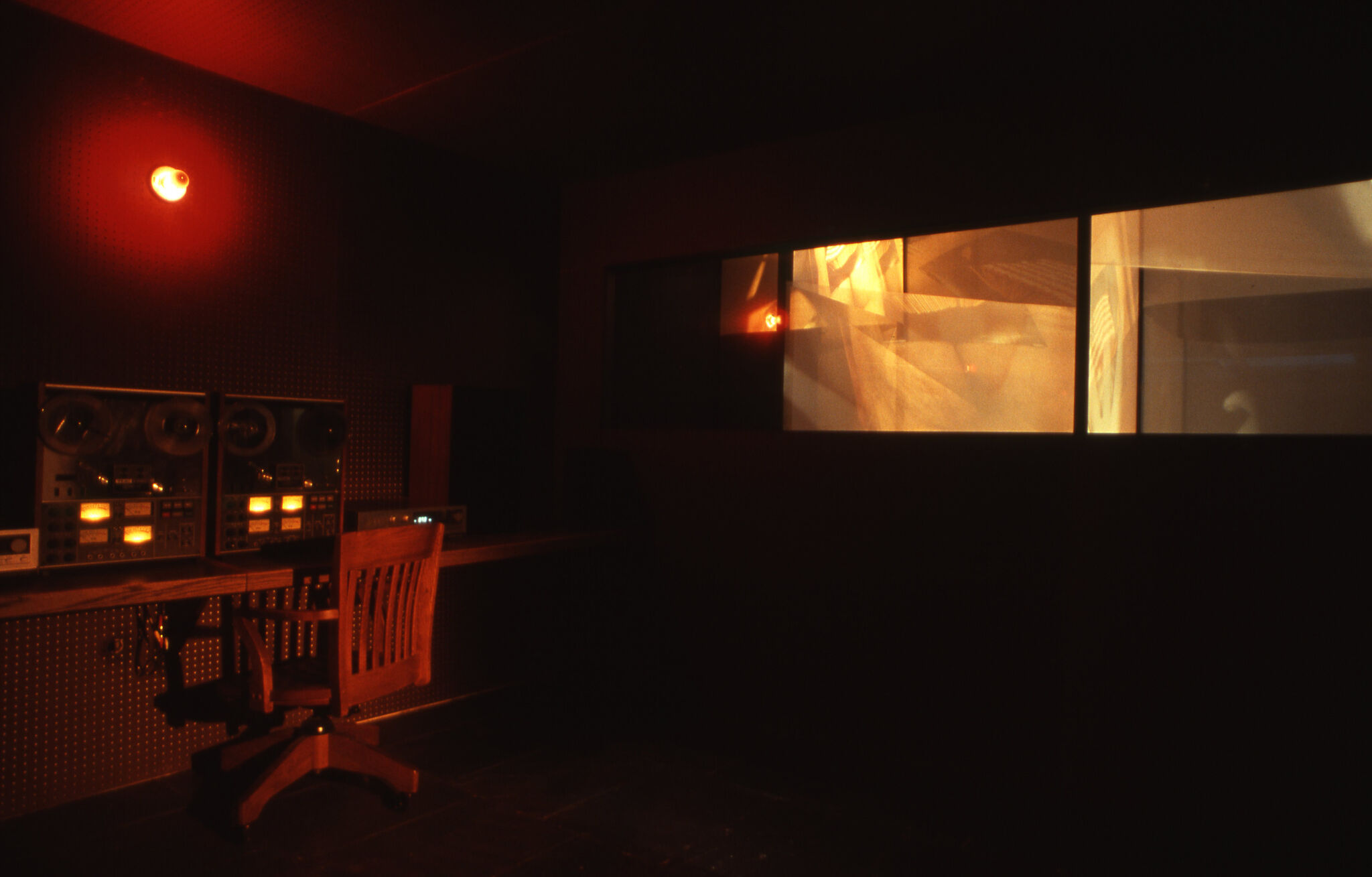 A dimly lit room with red lighting, a desk with speakers, and horizontal windows.