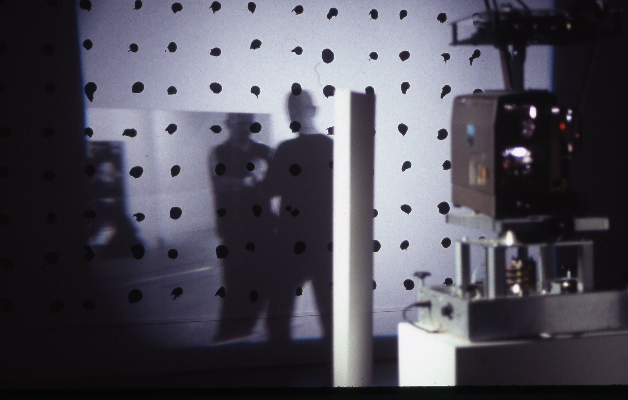 A projector projecting a black and white image on a white wall with black dots.