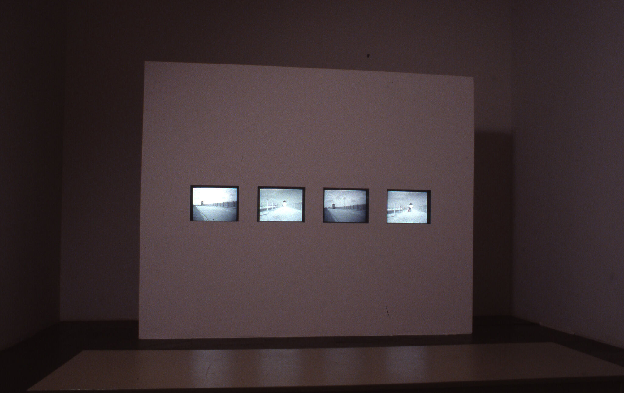 A white wall with a row of four screens displaying black and white views of streets.