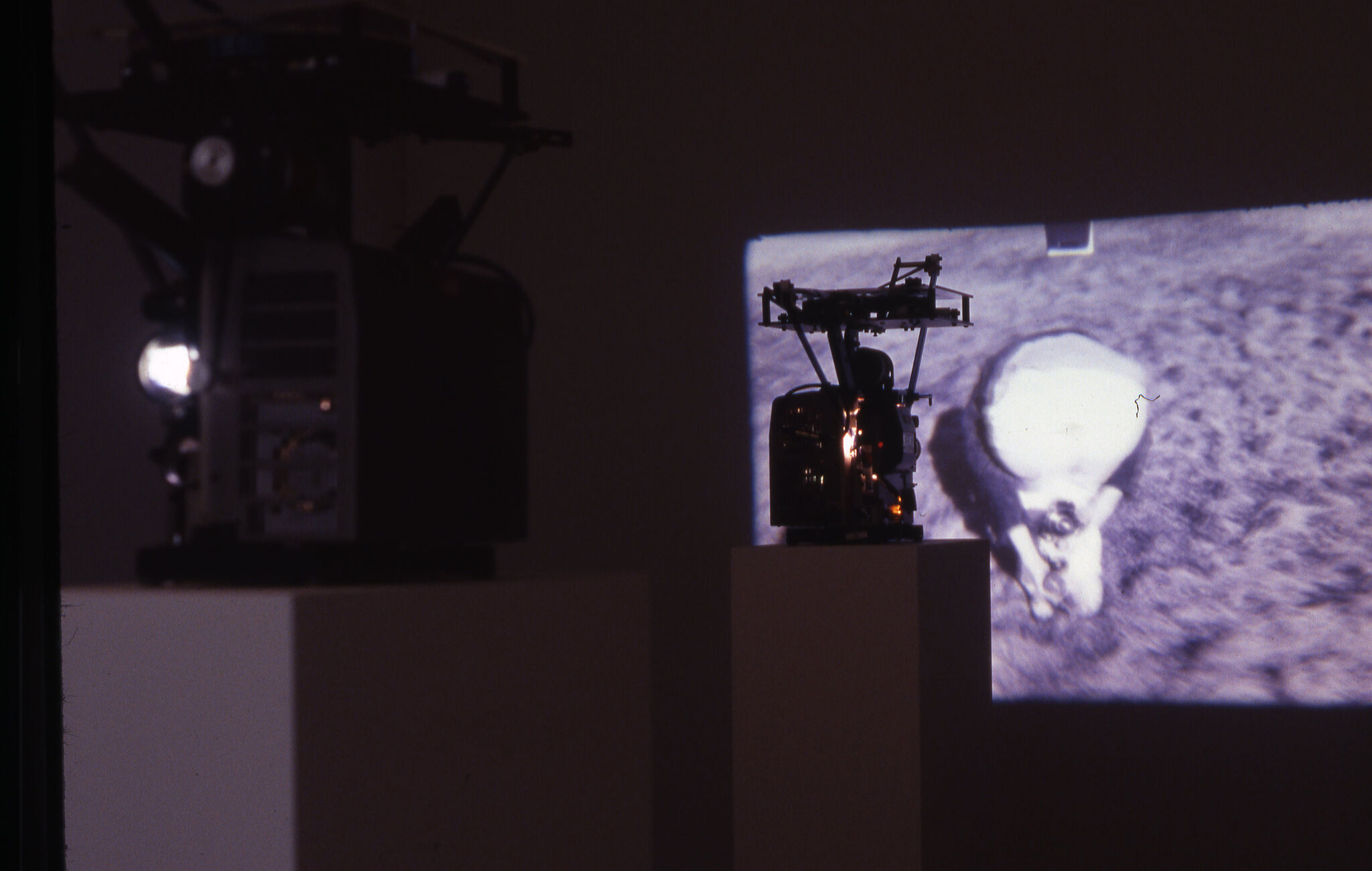 Two projectors and a black and white projected view on a wall in a gallery.
