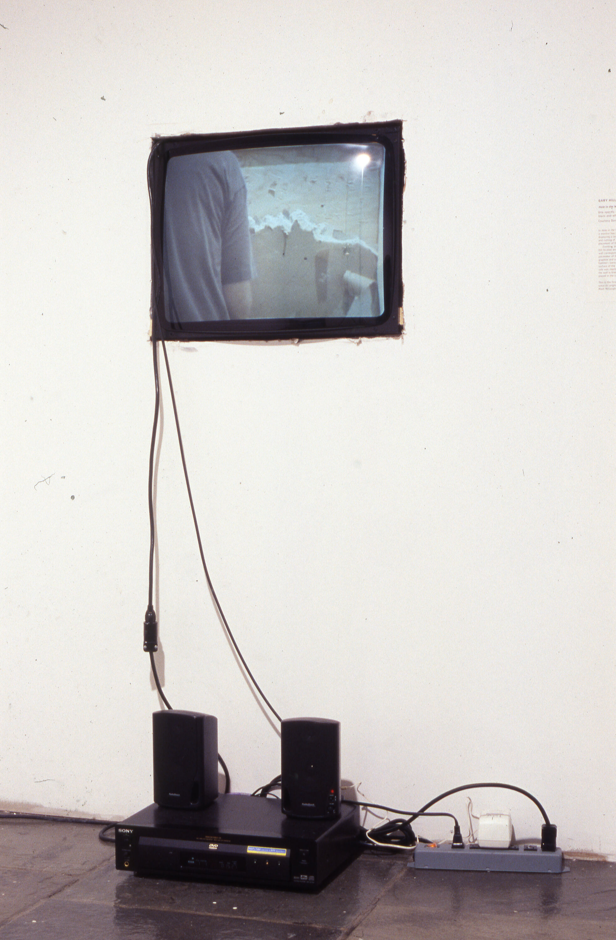 A screen on a white wall with black wires connecting it to two speakers on the ground.