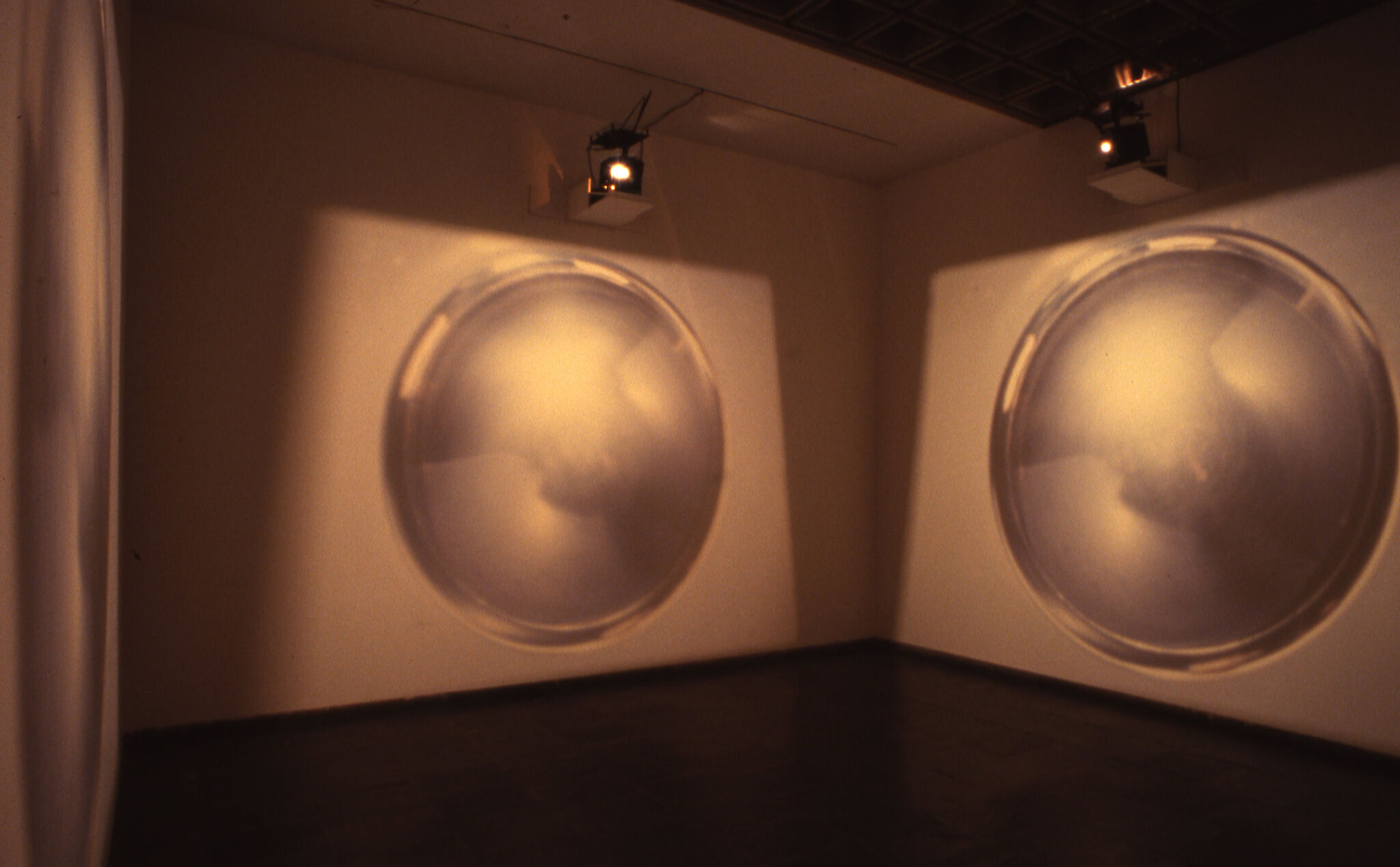 A dimly lit gallery space with large projections of a circle on the walls.