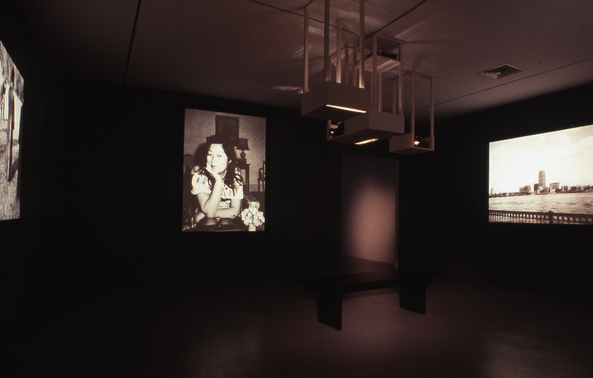 A dark gallery space with a projection of a portrait of a woman, and a projection of a cityscape.