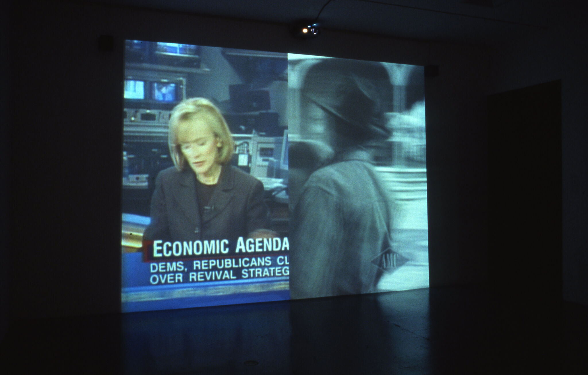 A screen split into two, with one side showing a news report and the other showing a black and white view of a figure passing by.