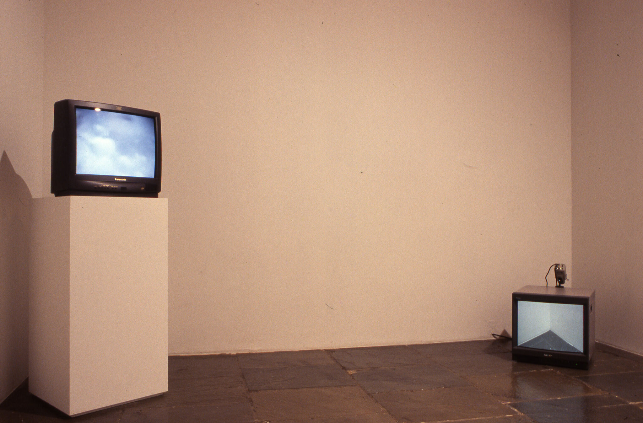 A small television set displayed on a pedestal along with another on the ground.