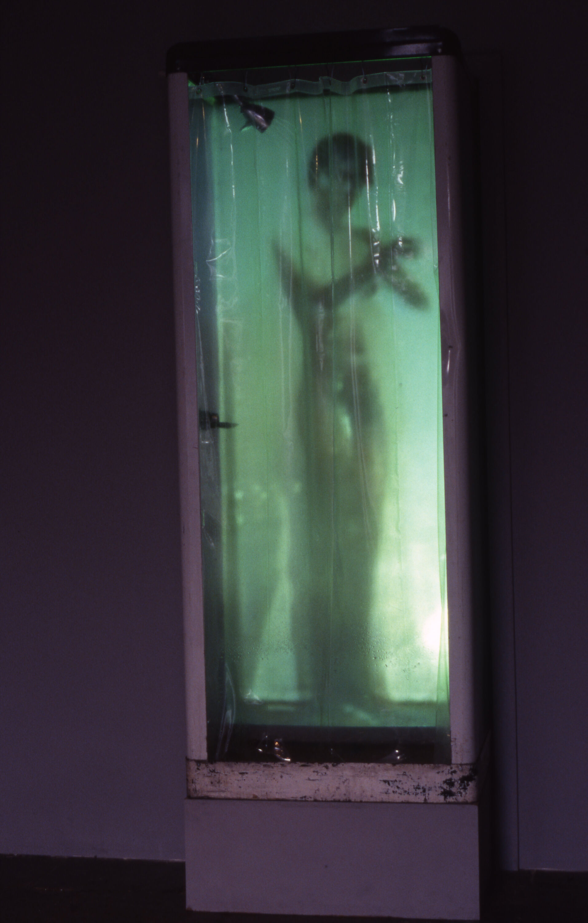 A long white frame with a plastic cover over a green-hued blurred image of a naked figure taking a shower.
