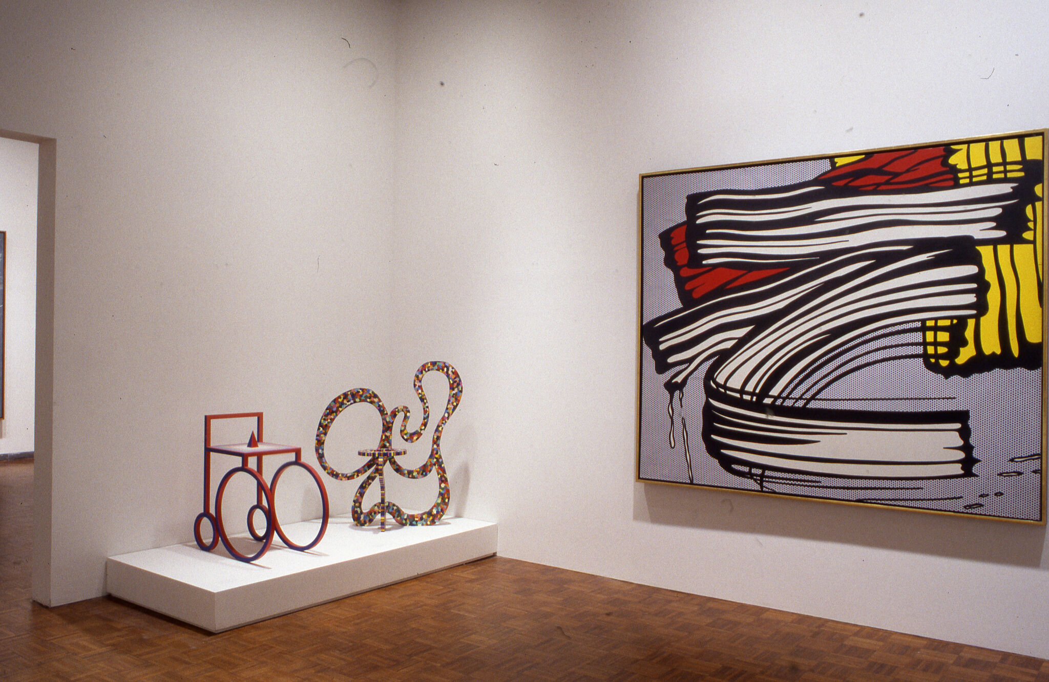 An abstract painting displayed alongside two sculptures in a gallery.