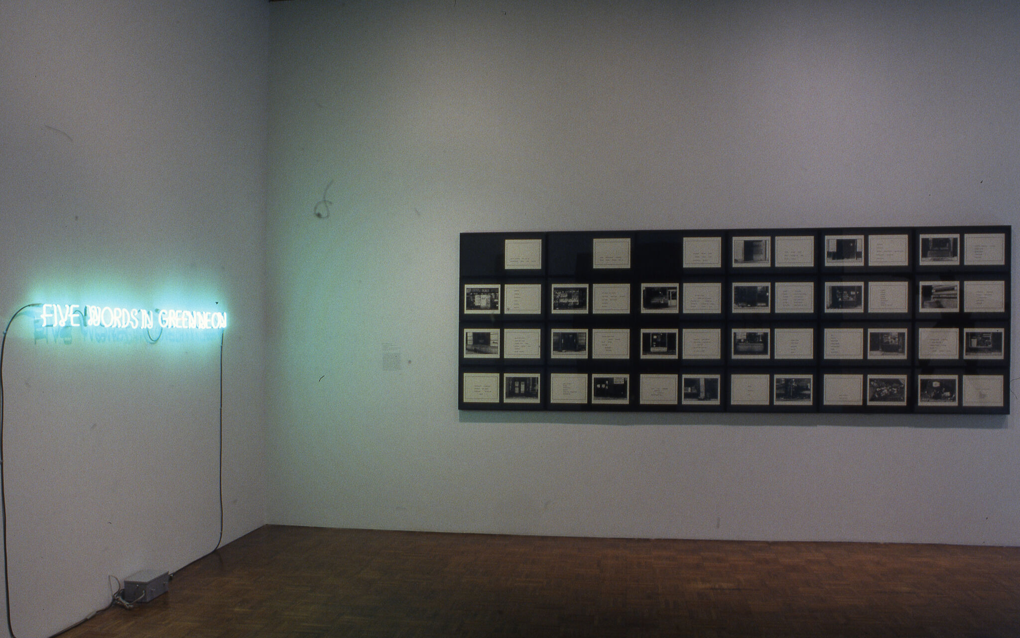 A gallery with a display of a green neon sign, along with a rectangular grid of photos.
