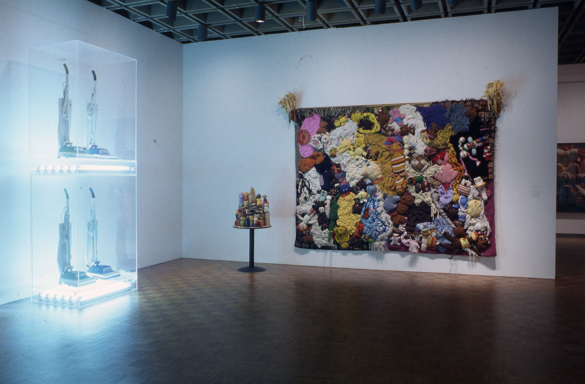 A large work of art made out of colorful textiles and knits, alongside a brightly lit sculpture displayed in a gallery.